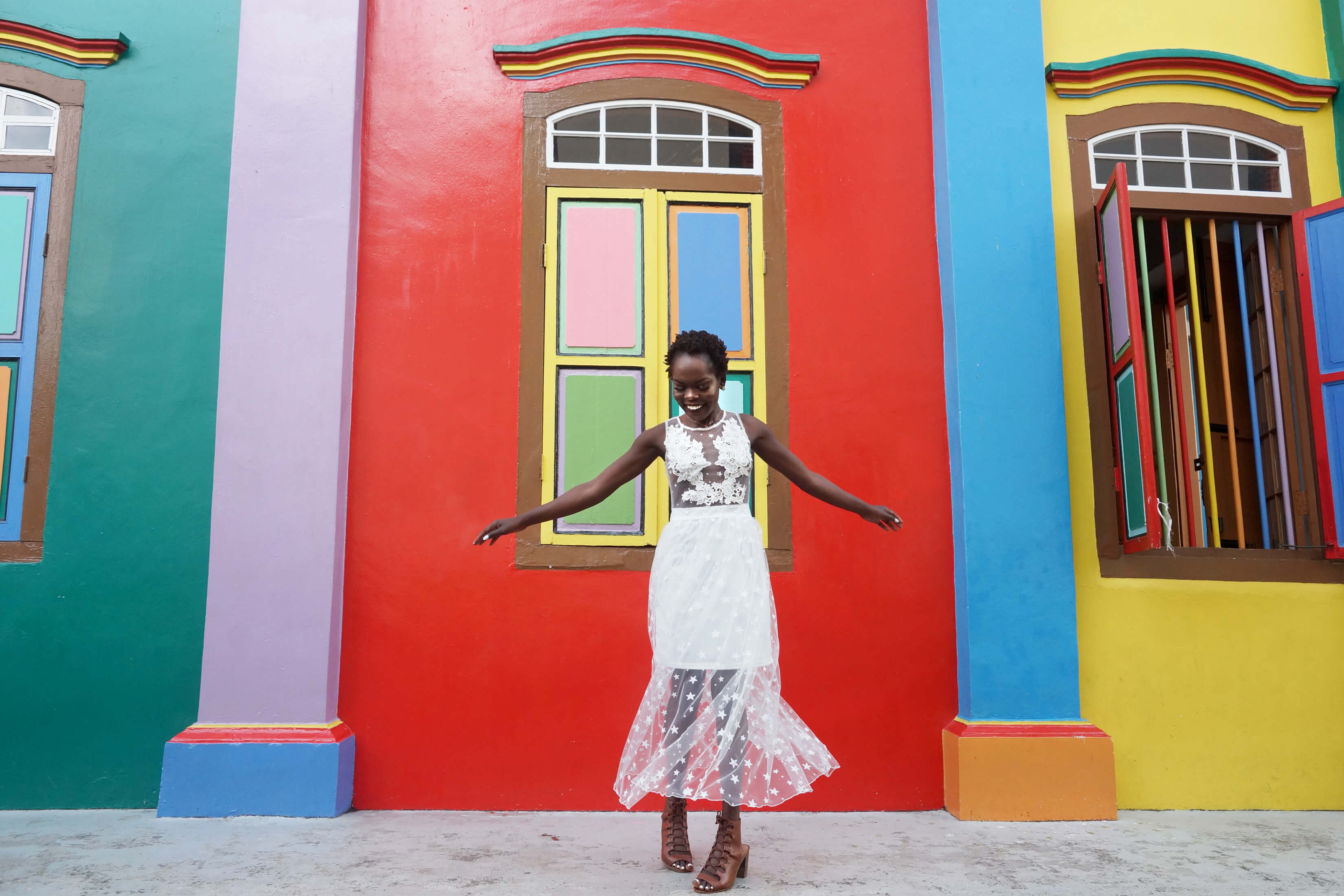 A woman dances in front of a colourful building in Singapore.