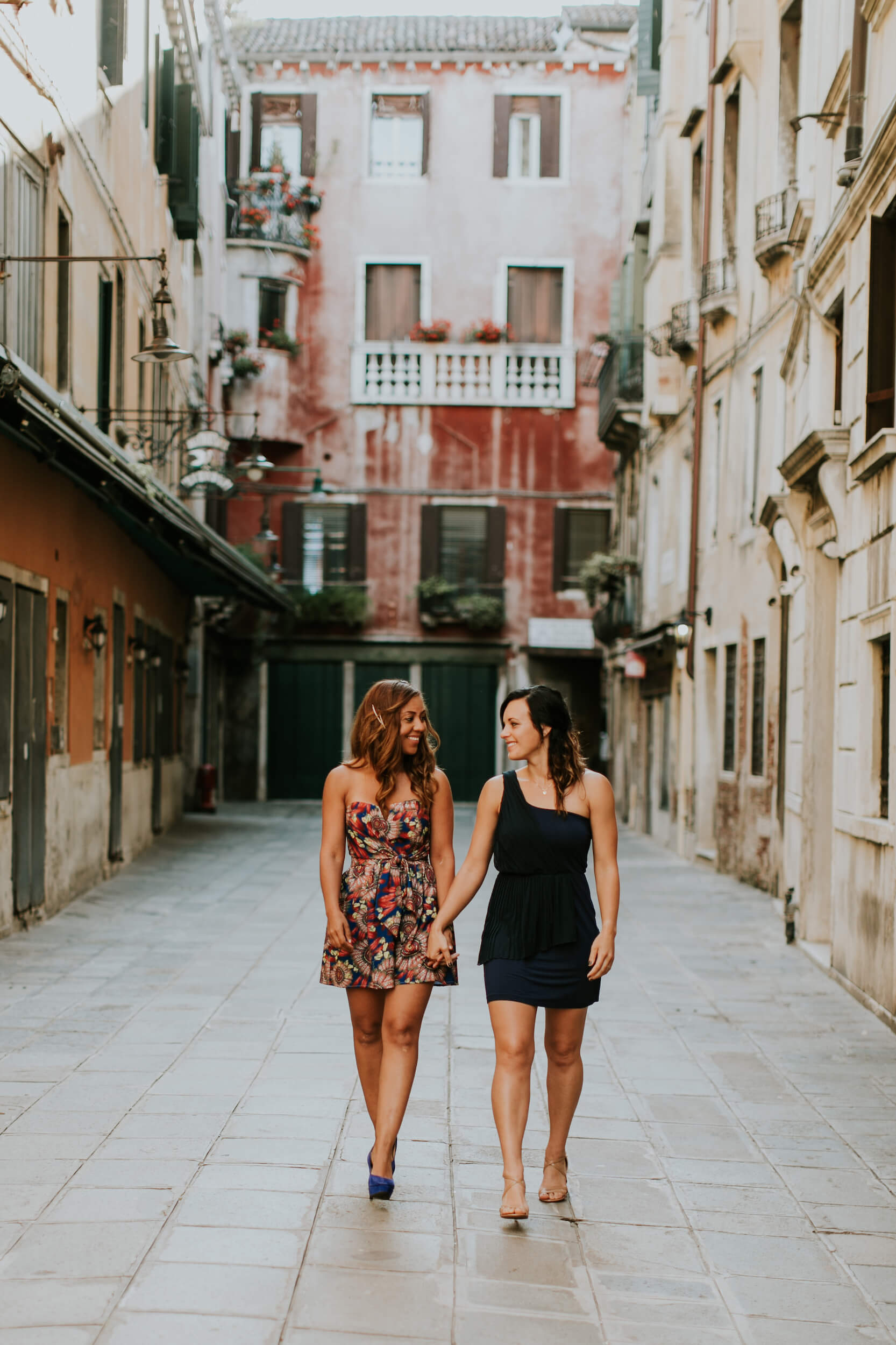 A Lesbian couple holds hands strolling the streets of Venice, Italy.