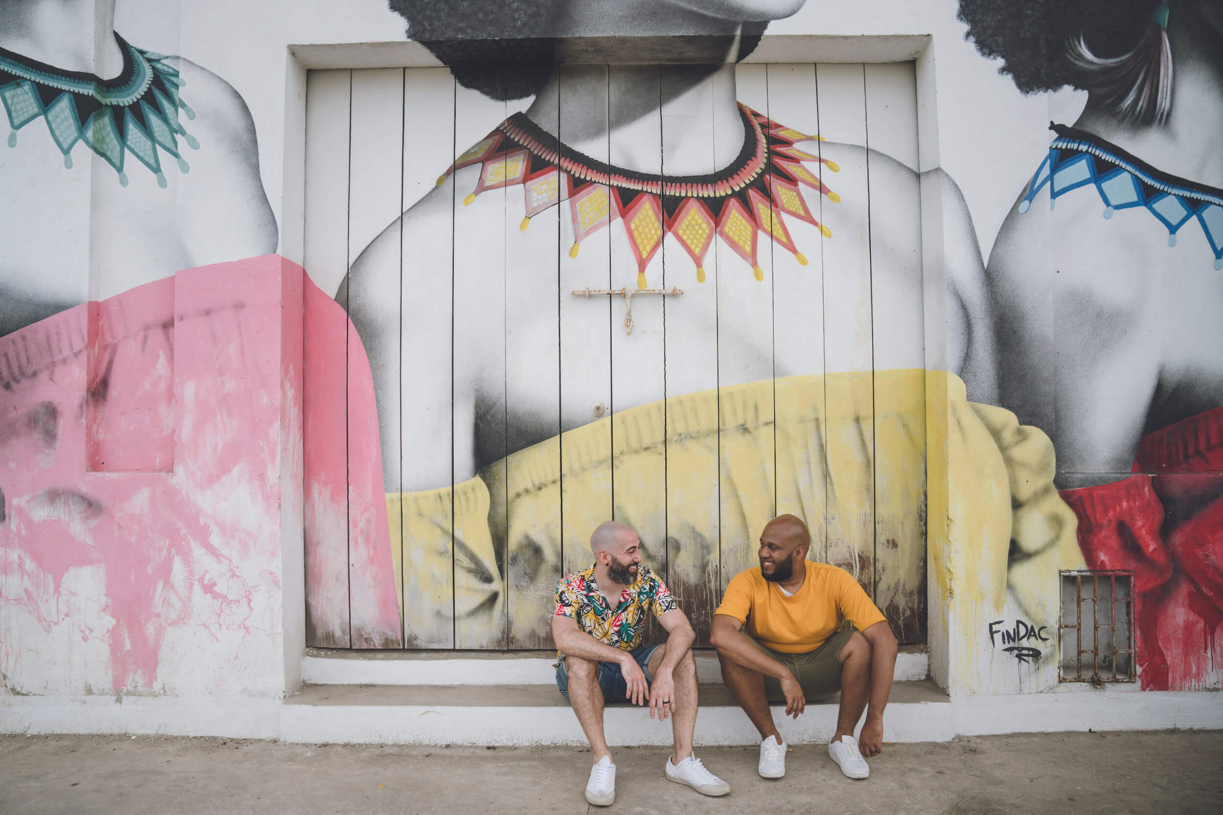 Two men sit on the sidewalk and smile at each other in Cartagena, Colombia.