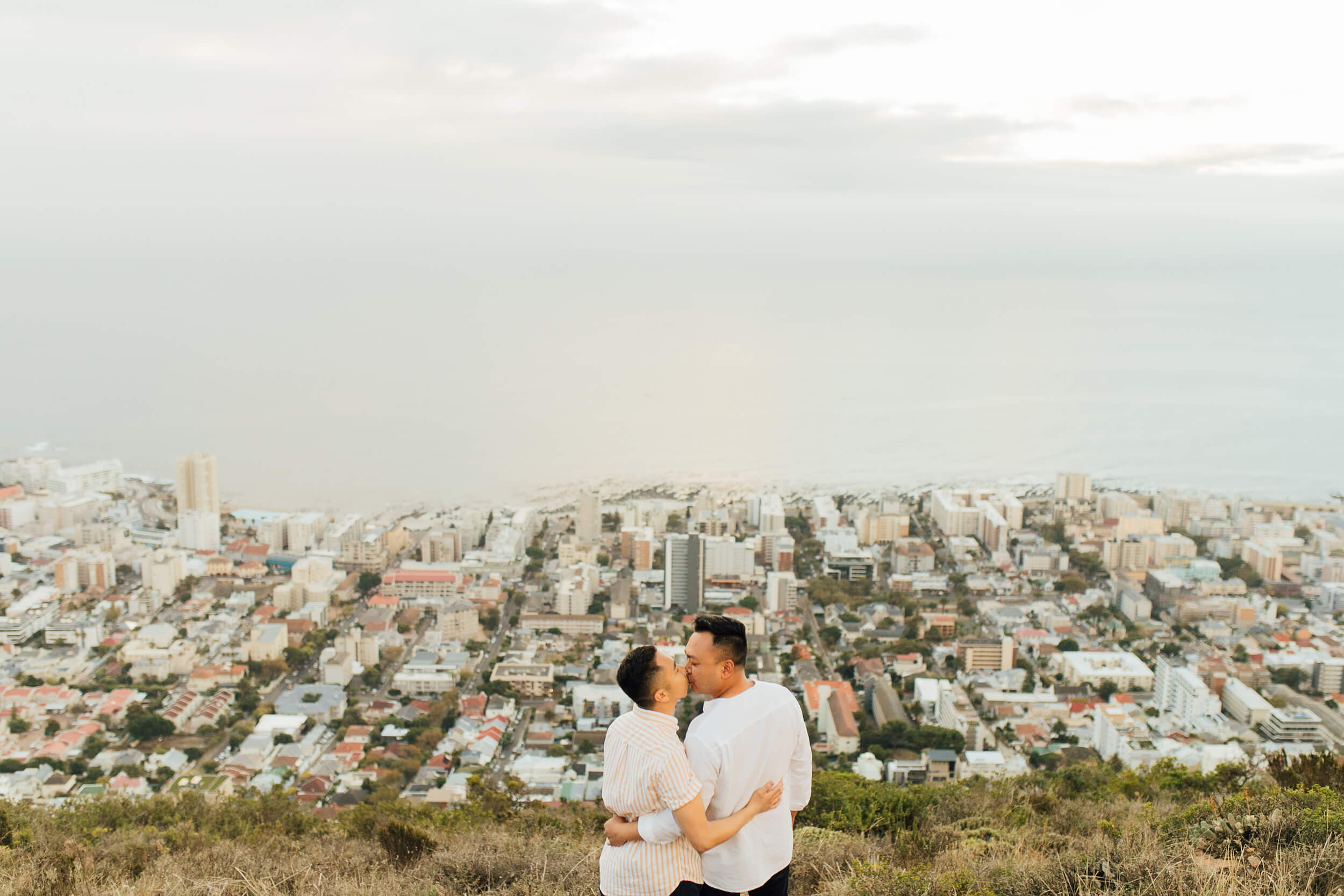 Two men kiss after getting engaged atop a hill overlooking Cape Town, South Africa.