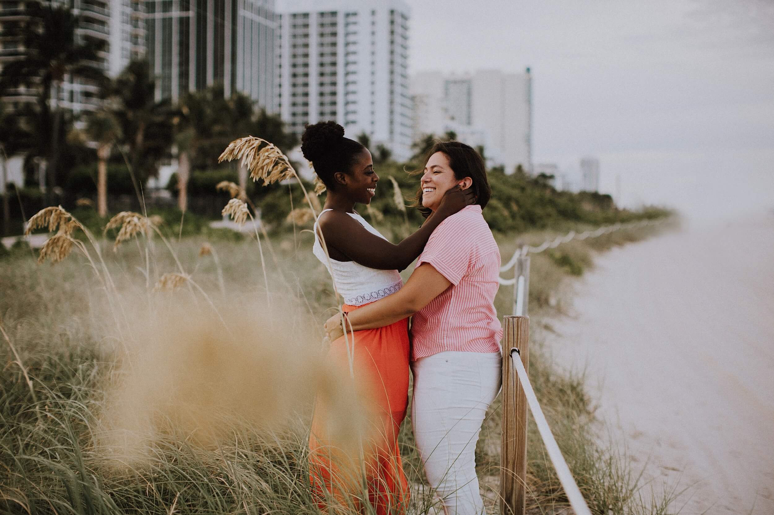 A Lesbian couple embrace on the beach in Miami, USA.