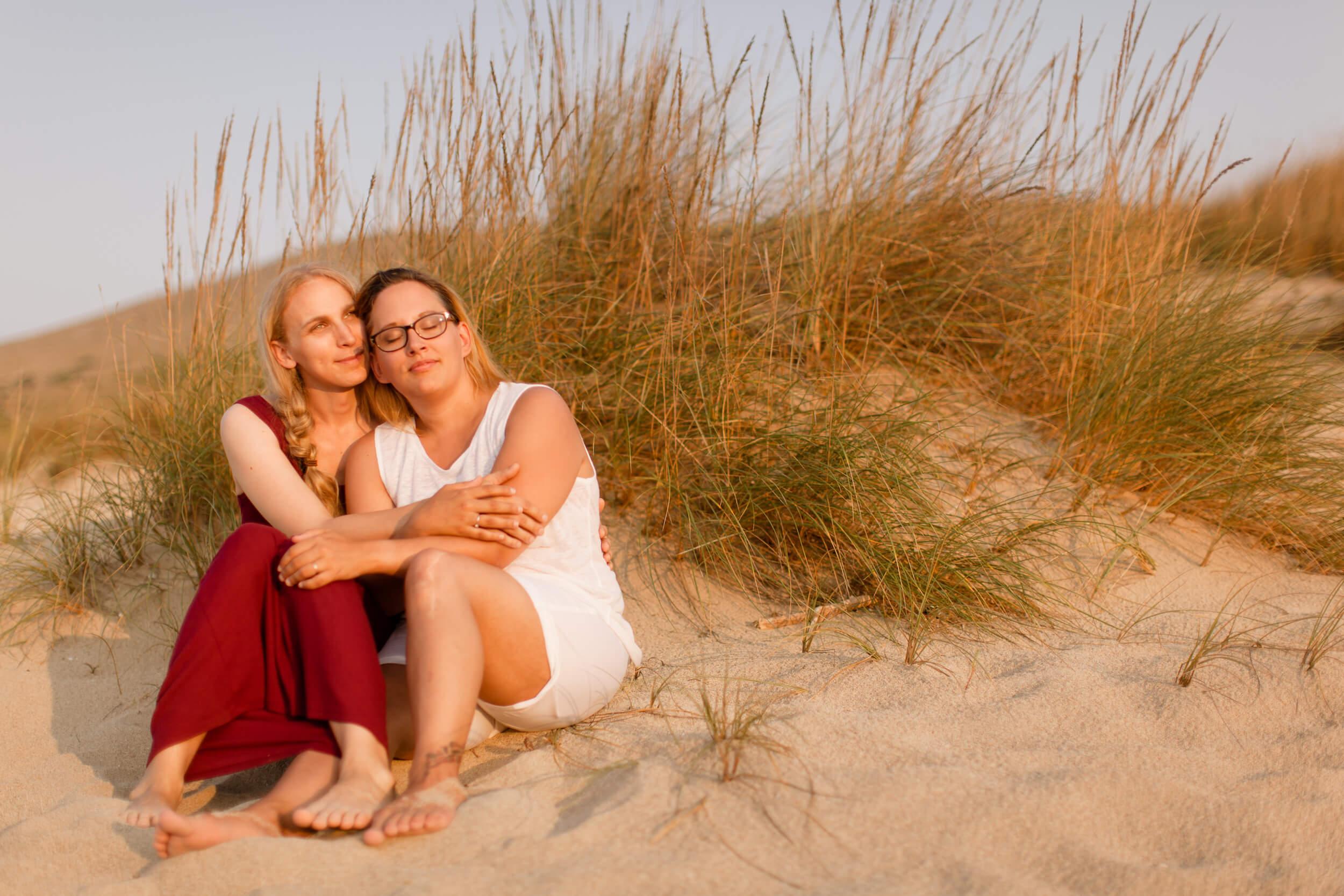 A female couple sits on the beach in Palma de Mallorca, Spain.