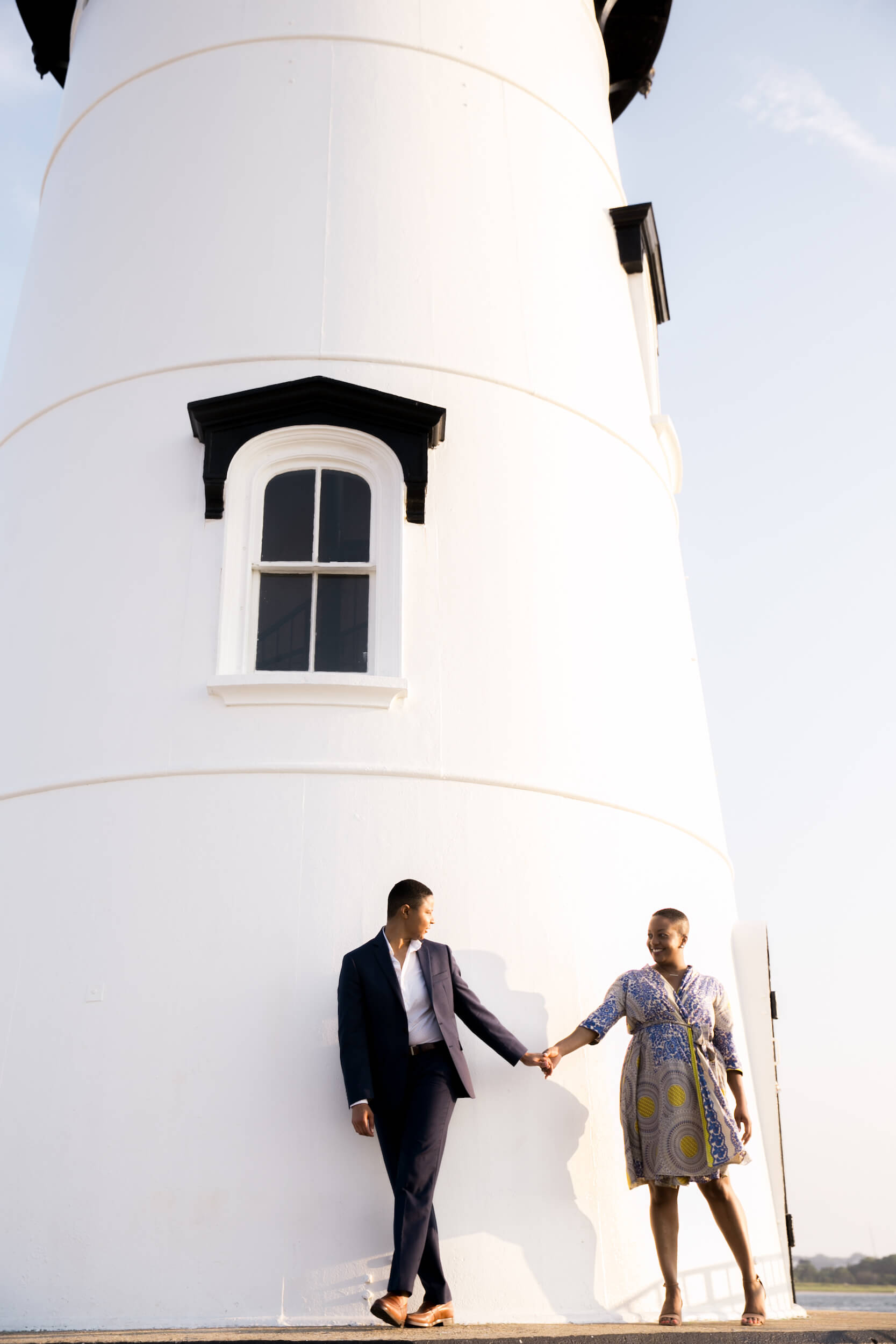 A Lesbian couple hold hands while walking around a lighthouse in Martha's Vineyard, USA.