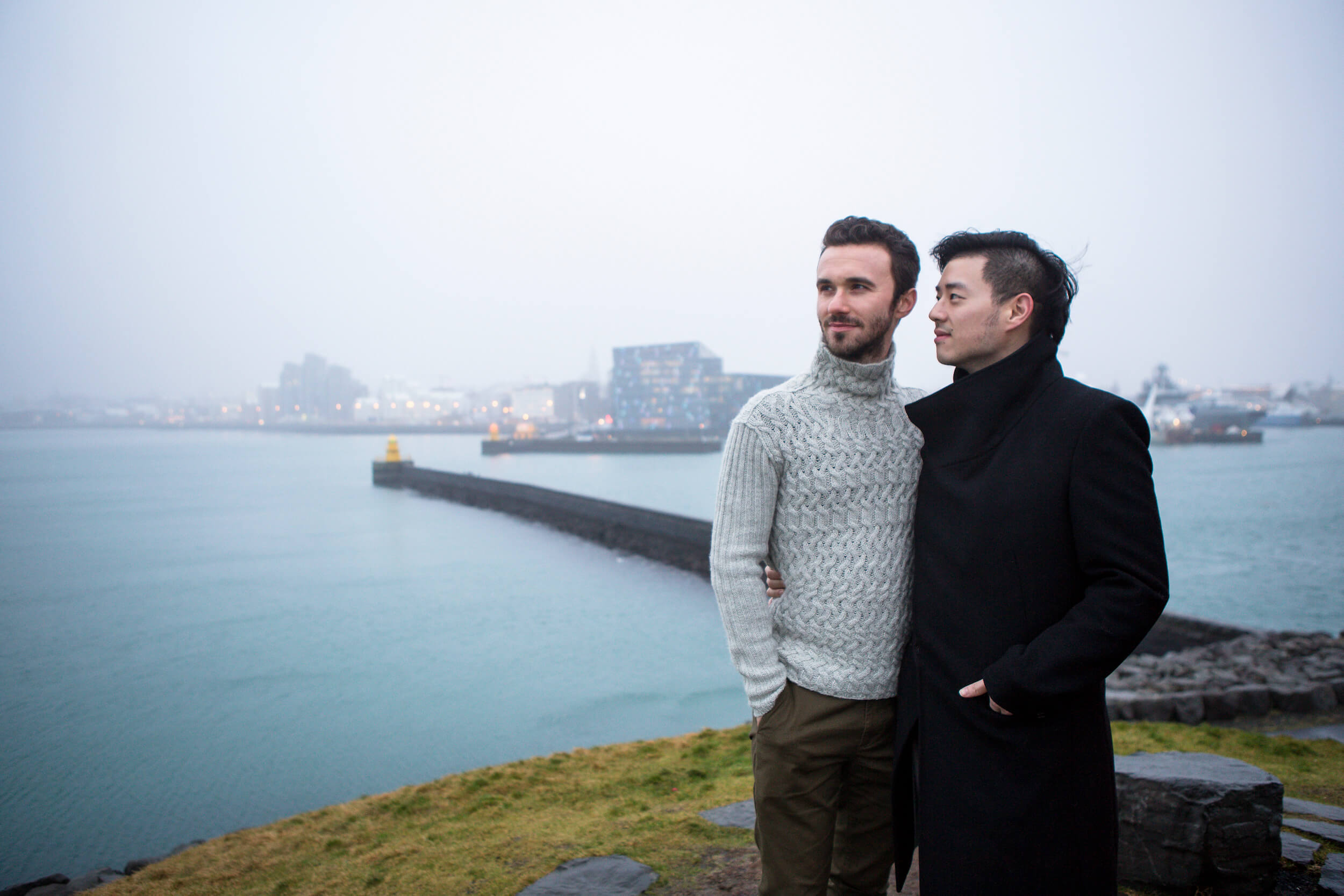 A male couple hold each other looking over the harbour in Reykjavik, Iceland.