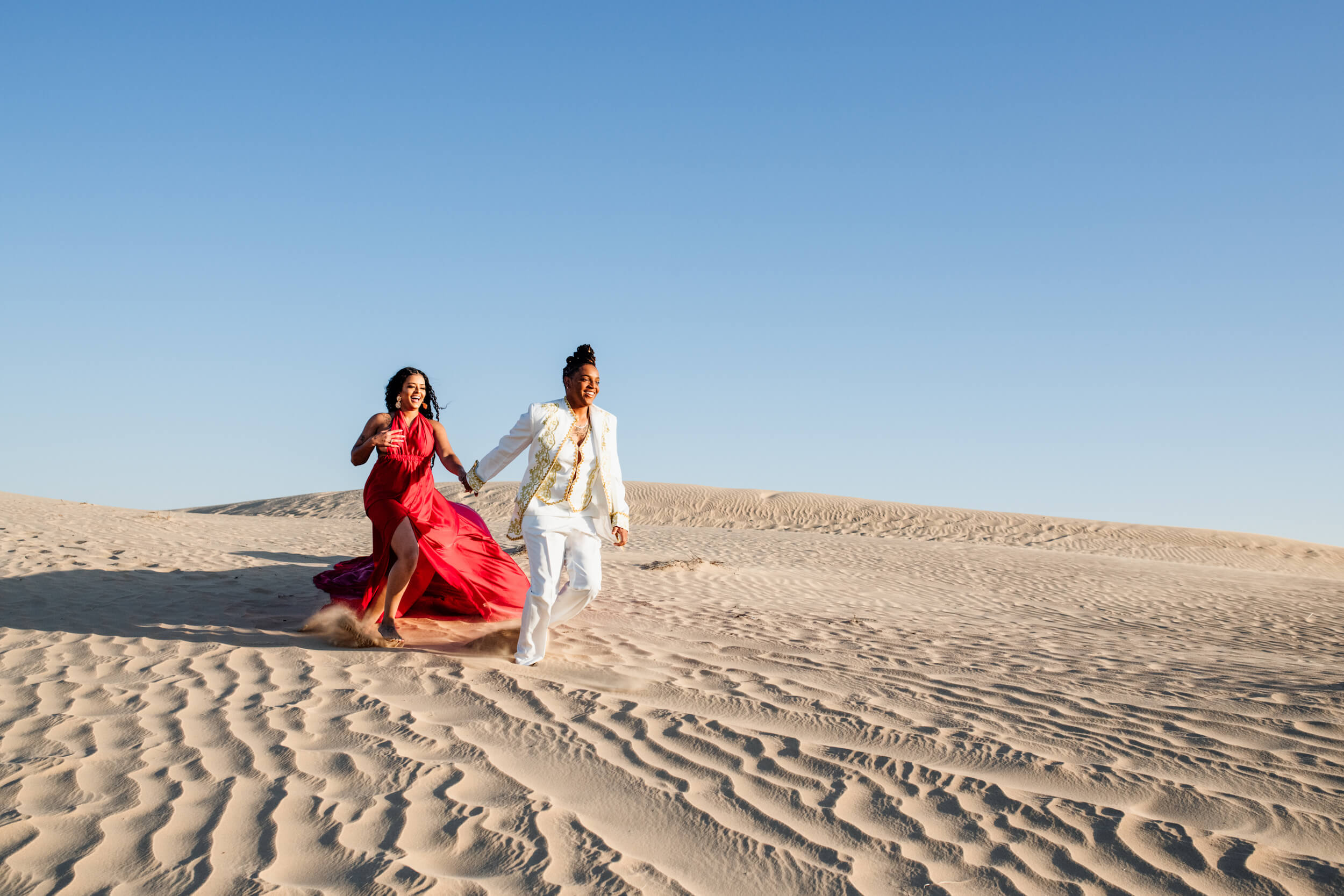 A Lesbian couple hold hands and laughing while running across the sand dunes in Dubai, UAE.