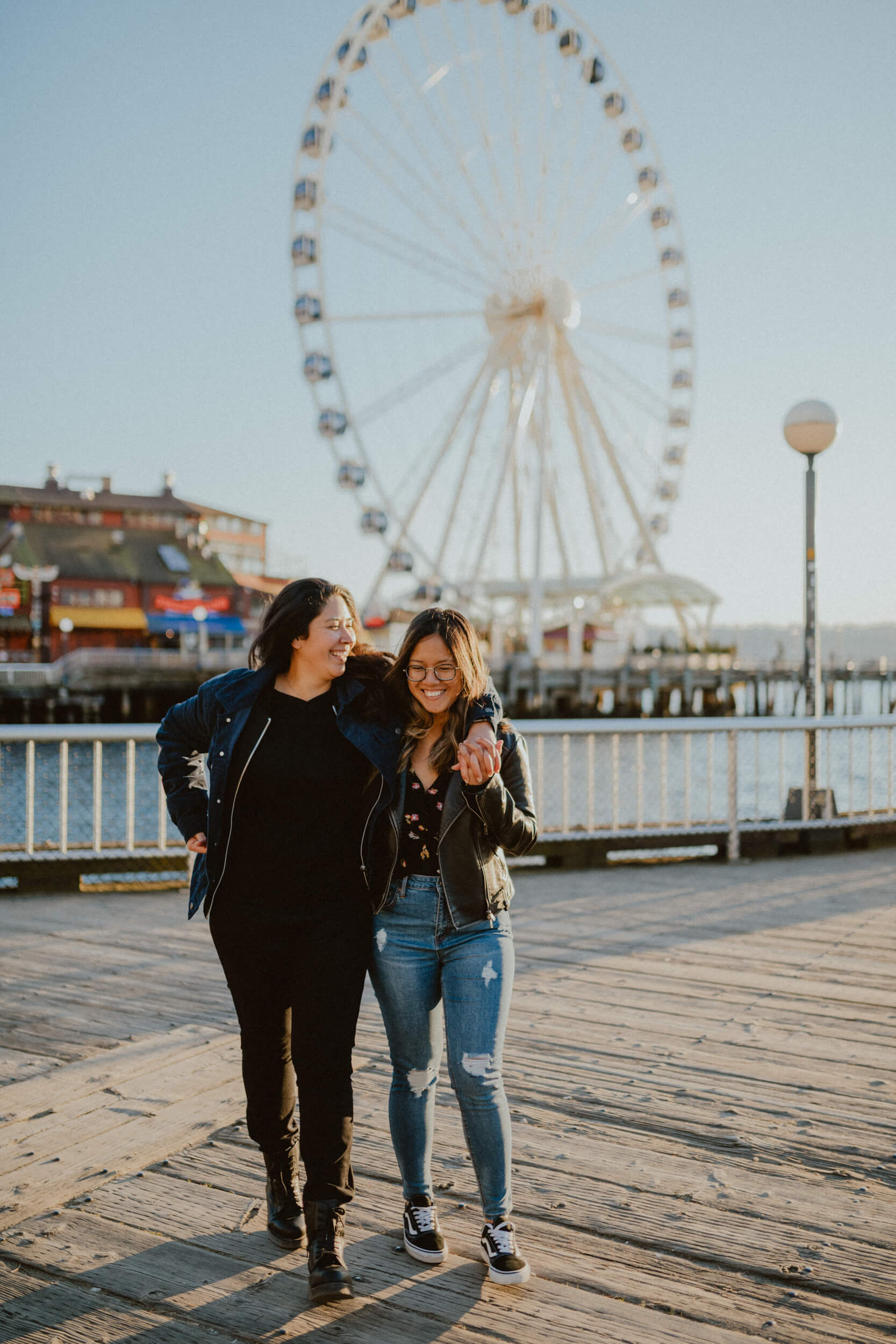 a couple hugs while walking on the boardwalk in Seattle, USA.