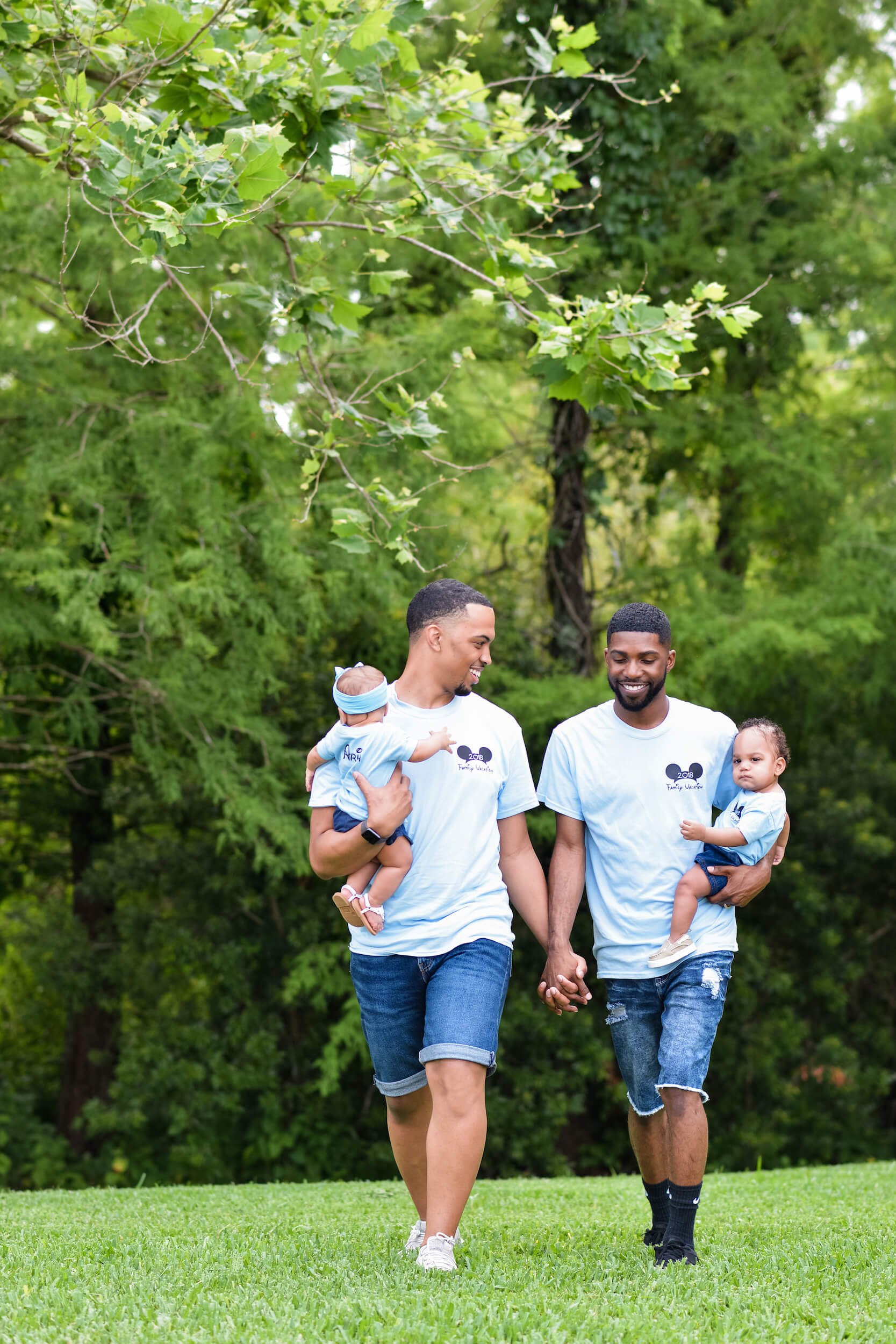 Two dads hold hands and their babies in Orlando, USA.