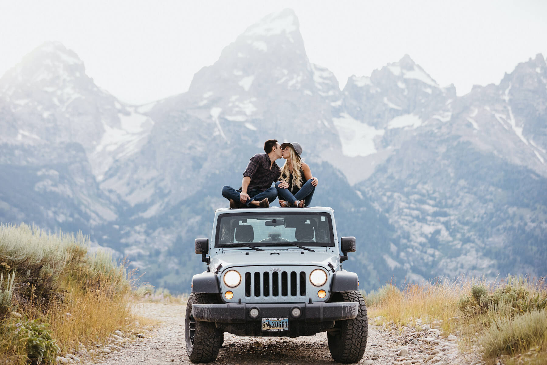 Couple hugging and sitting on a jeep in front of mountains in Jackson Hole