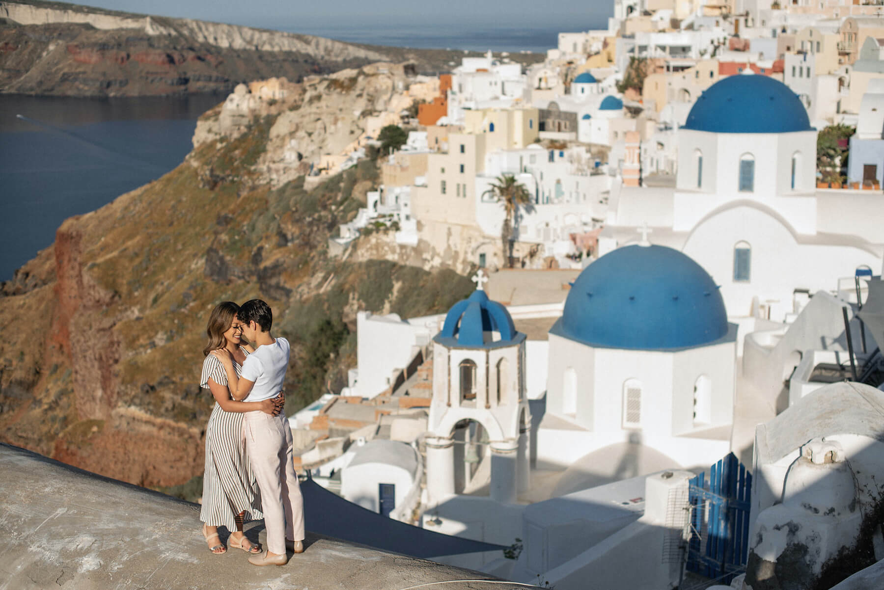 Couple enjoying the views surrounded by beautiful blue and white houses in Santorini