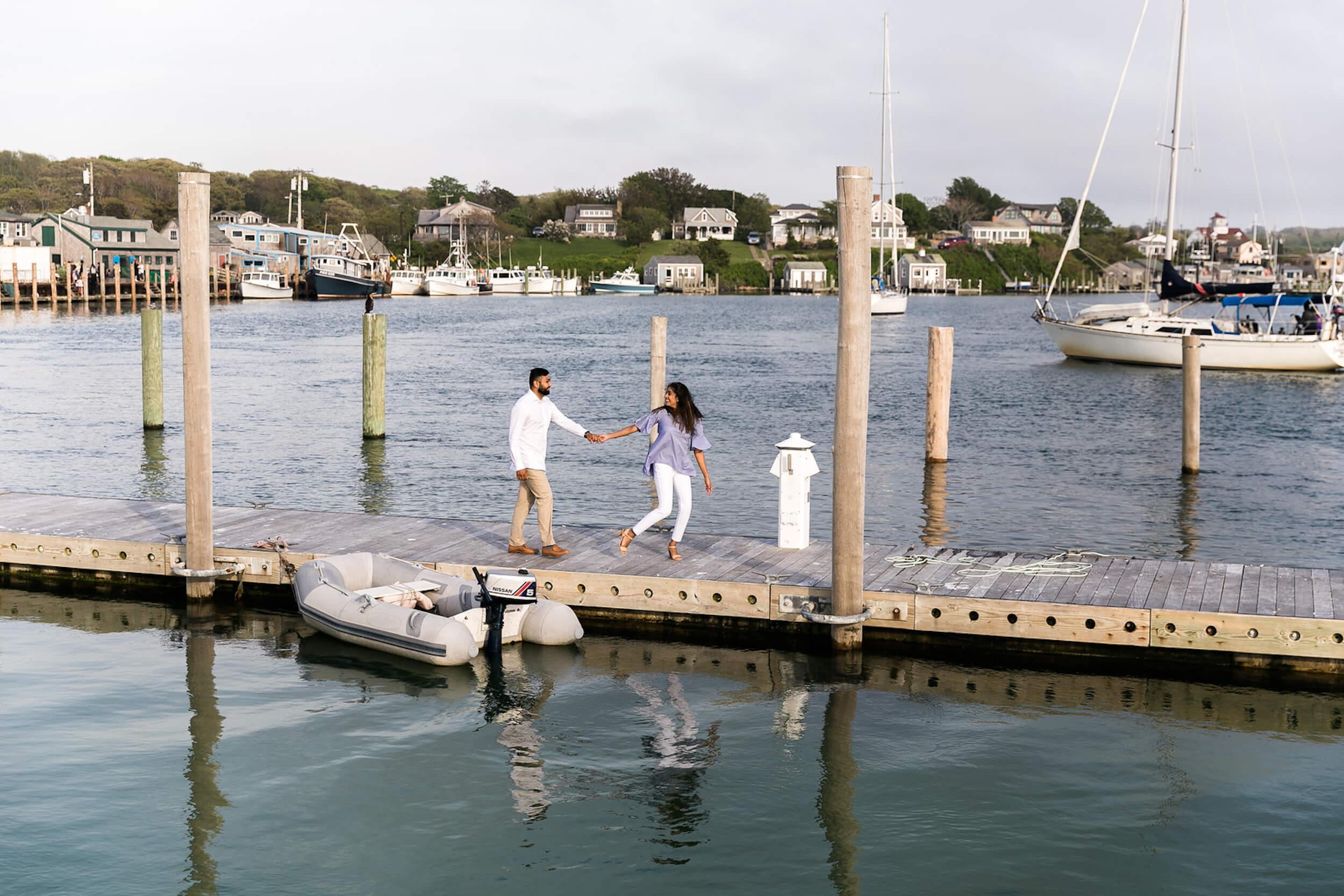 A couple walks along a dock in Martha's Vineyard, Massachusetts, USA.
