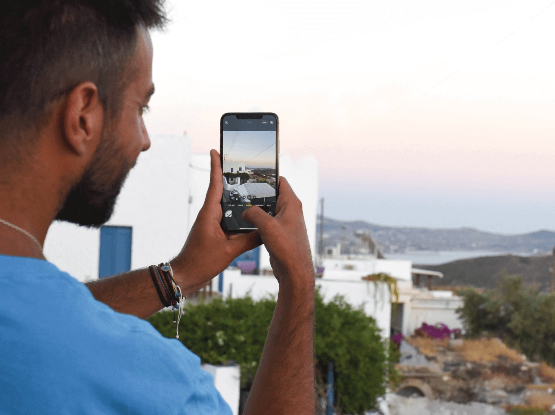 Hands holding an iPhone and taking a photo in Santorini