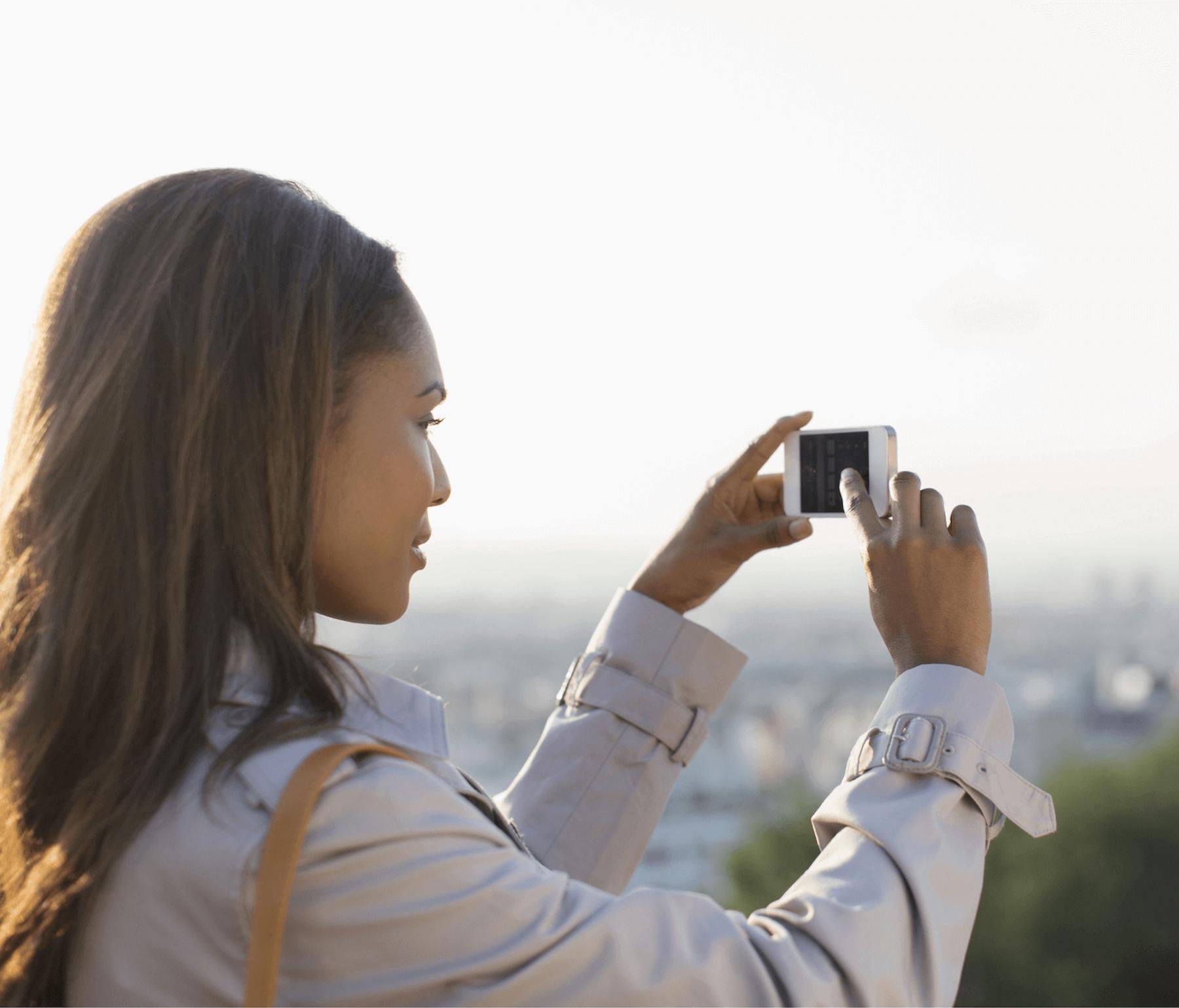 Woman taking Santorini sunset photo with iPhone
