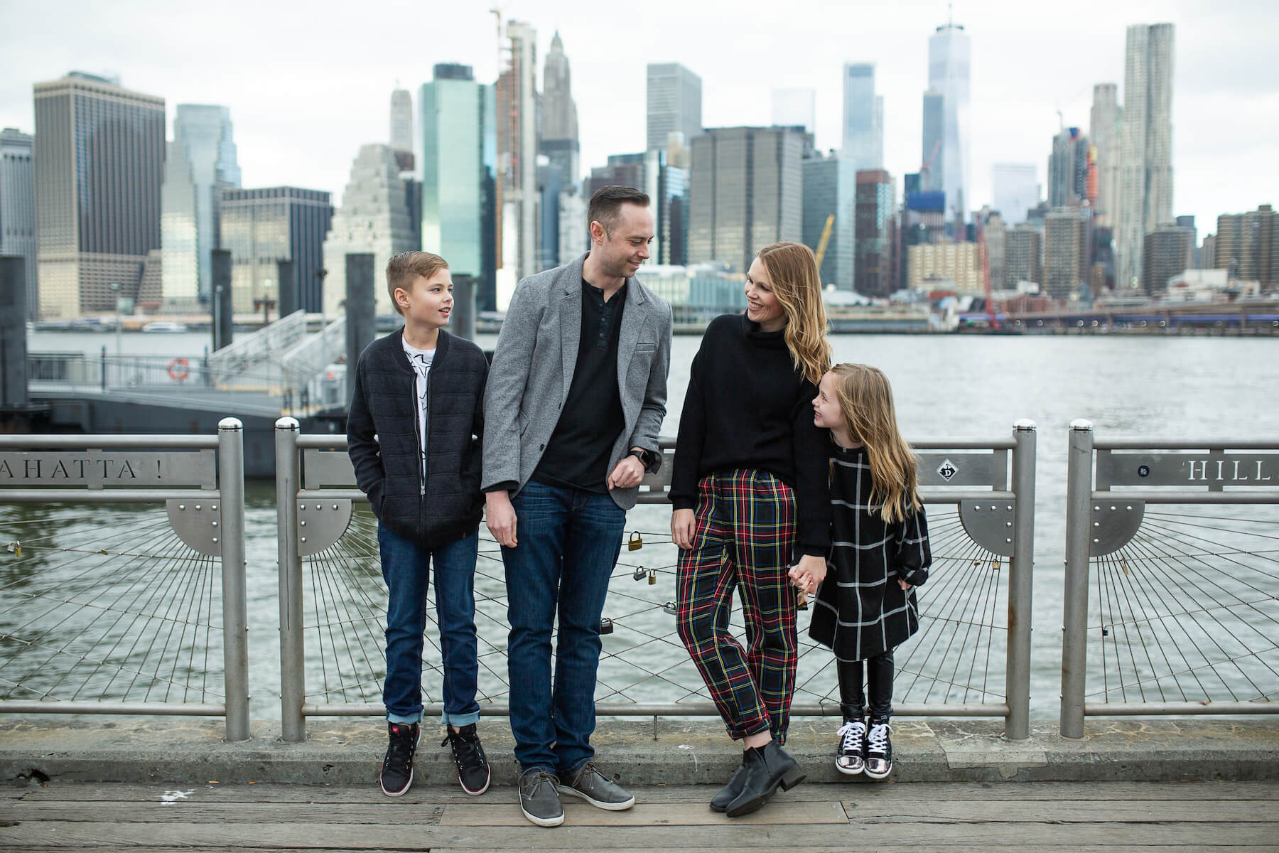 Family in NYC with skyline of NYC in the background