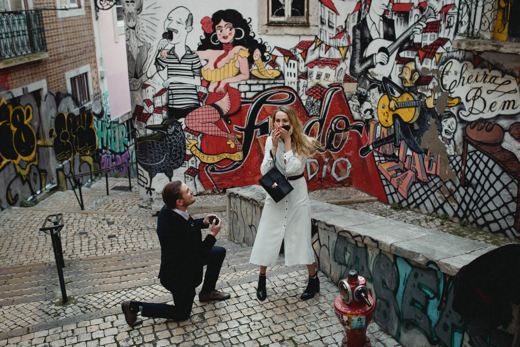Man is on one knee proposing to the woman, who looks surprised. They are standing in front of a colourful wall in Lisbon.