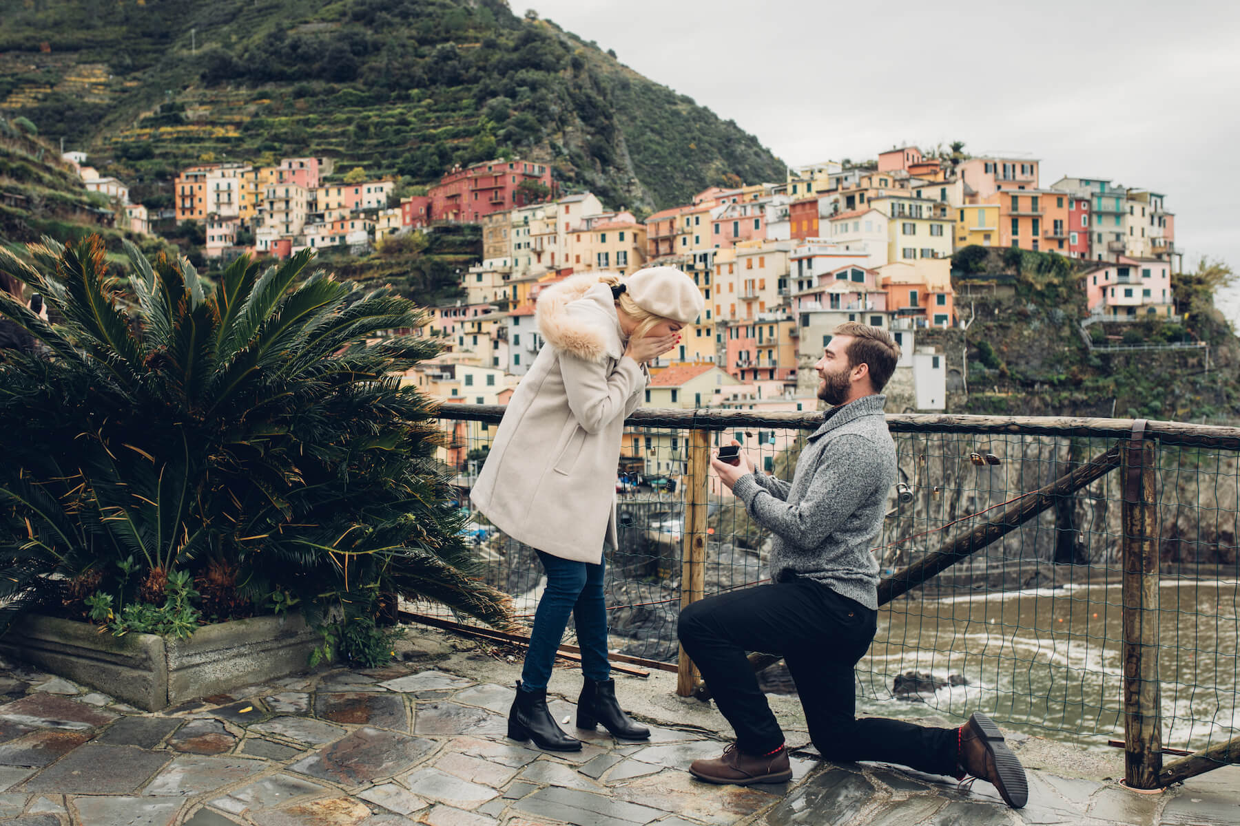 A man is proposing to a woman on a lookout point in Cinque Terre. Both are wearing weather appropriate outfits. The woman is wearing a white coat.