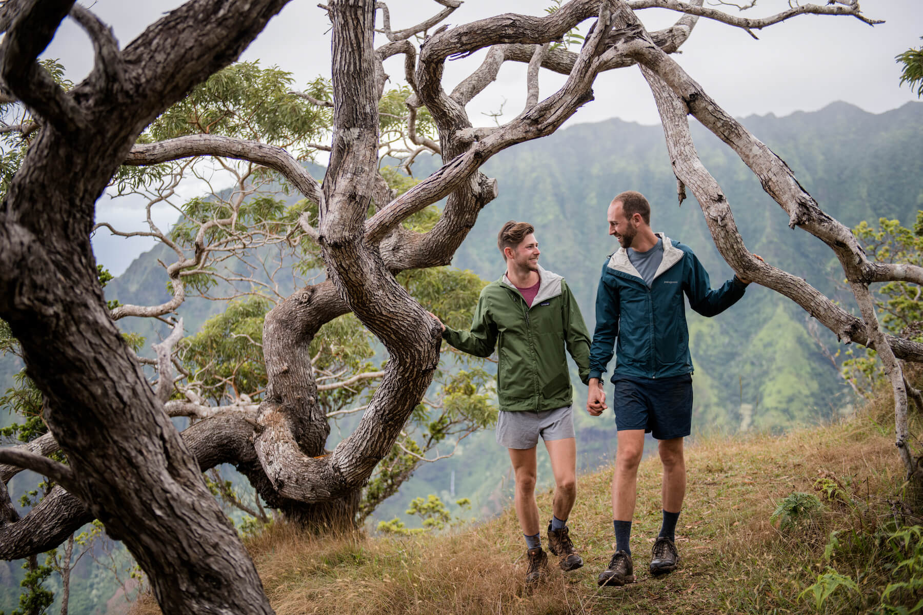 A man is proposing to a man while on a hike in Kauai. The one one man is kneeling. Both men are wearing hiking outfits.