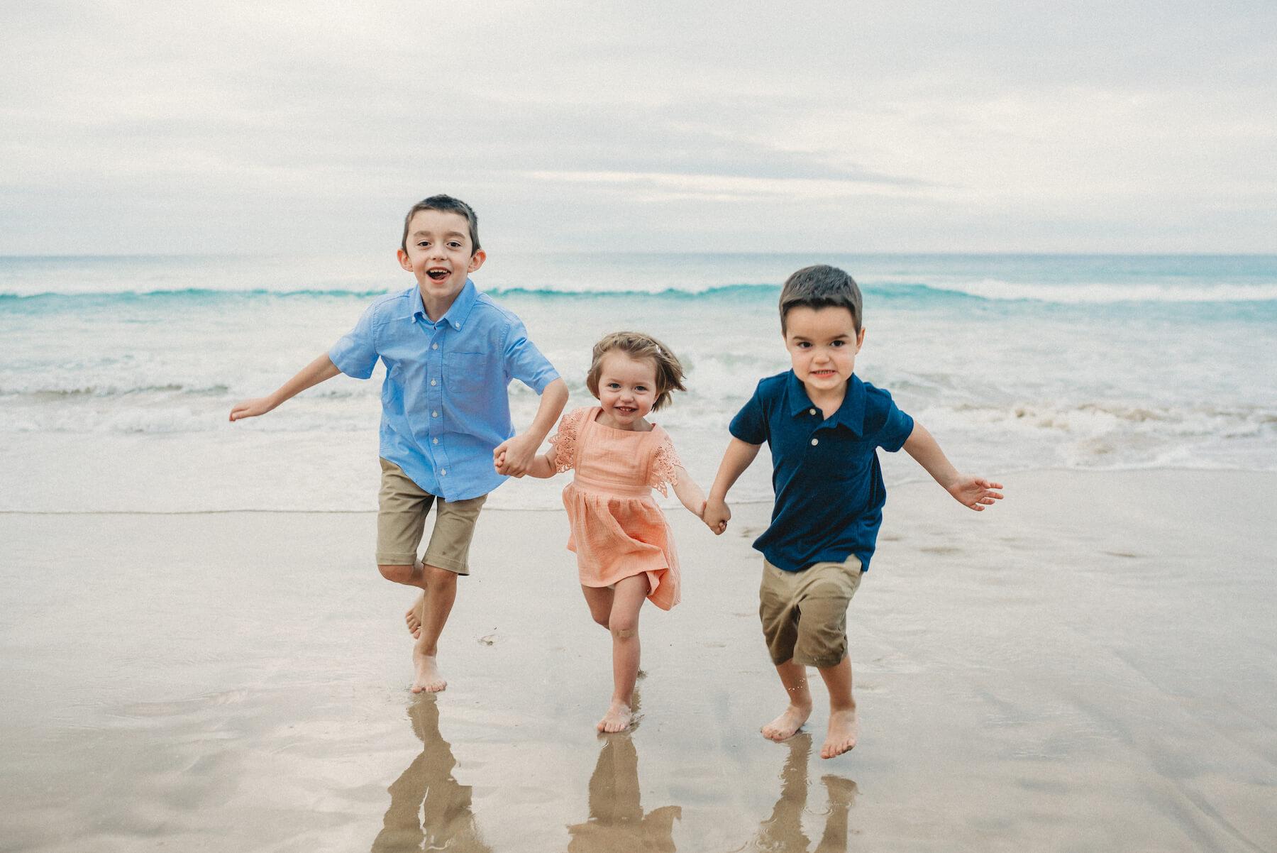 Kids running on the beach in Kona, Hawaii
