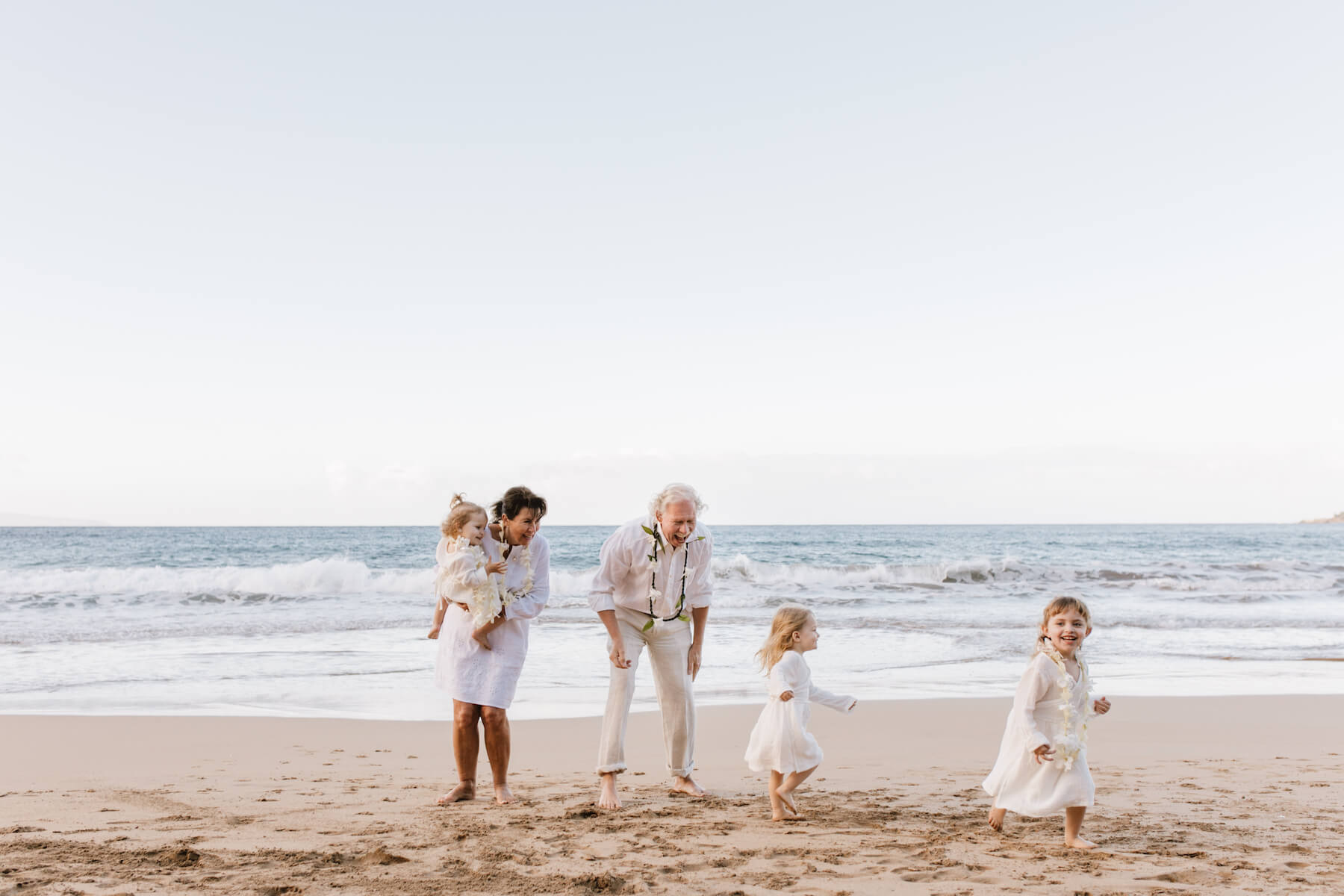 grandparents with their grandkids running on the beach in Maui, Hawaii