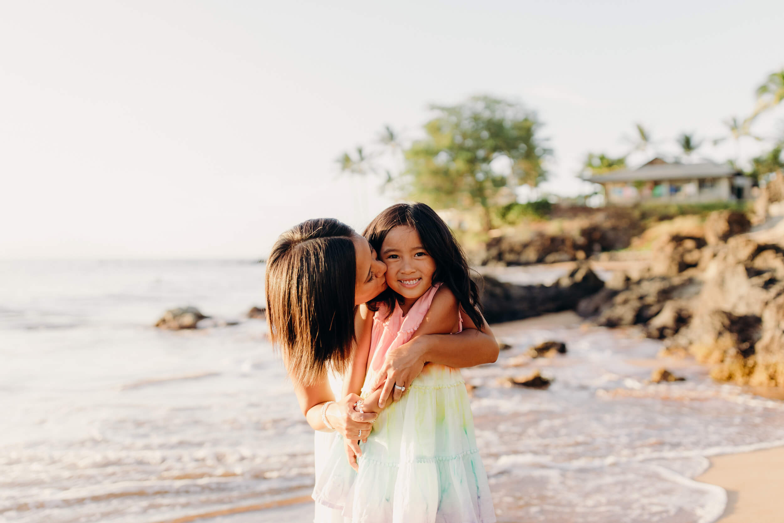 Mother kissing her daughter on the cheek on a beach in Maui