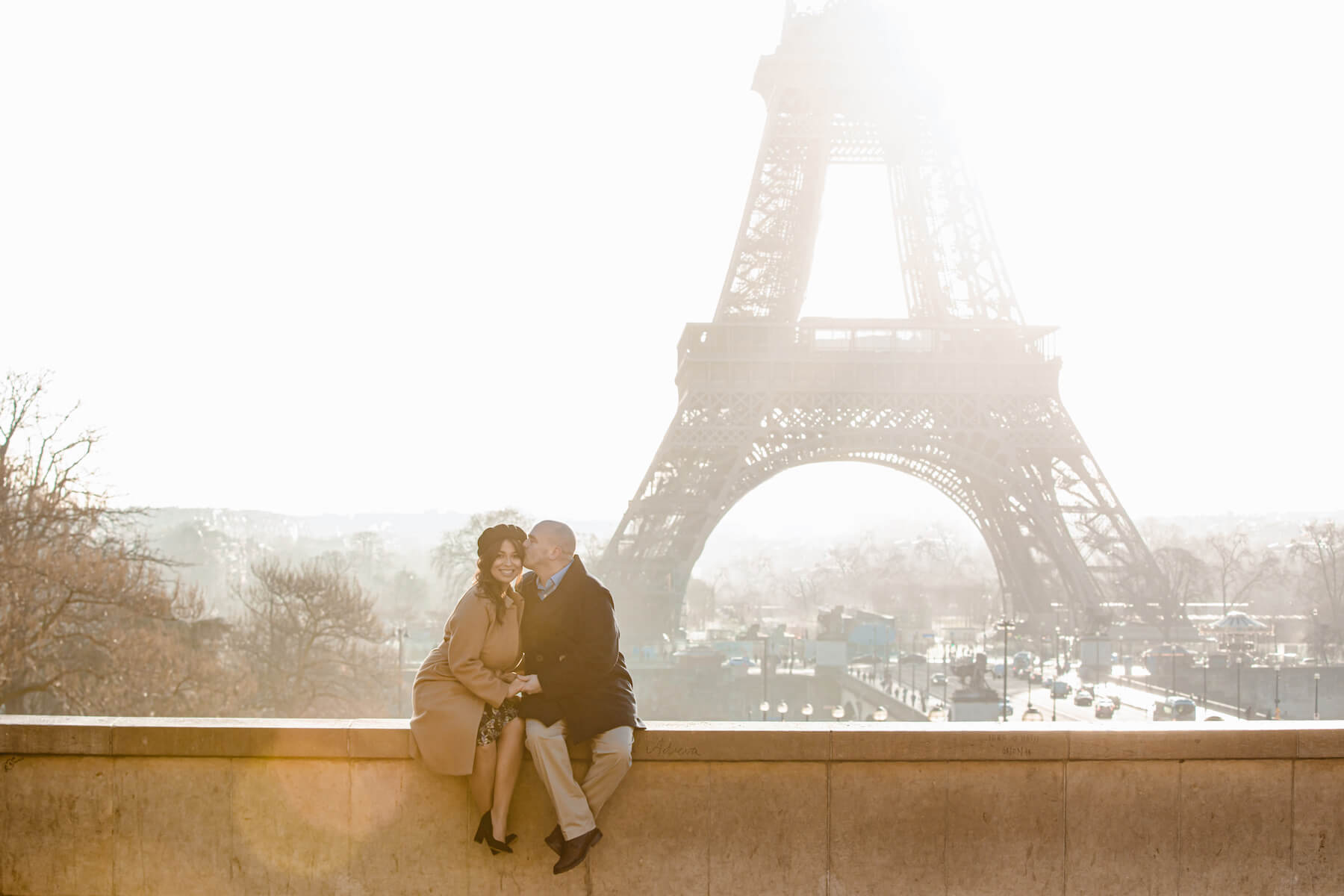 couple sitting on a ledge with the Eiffel tower in the background in Paris, France