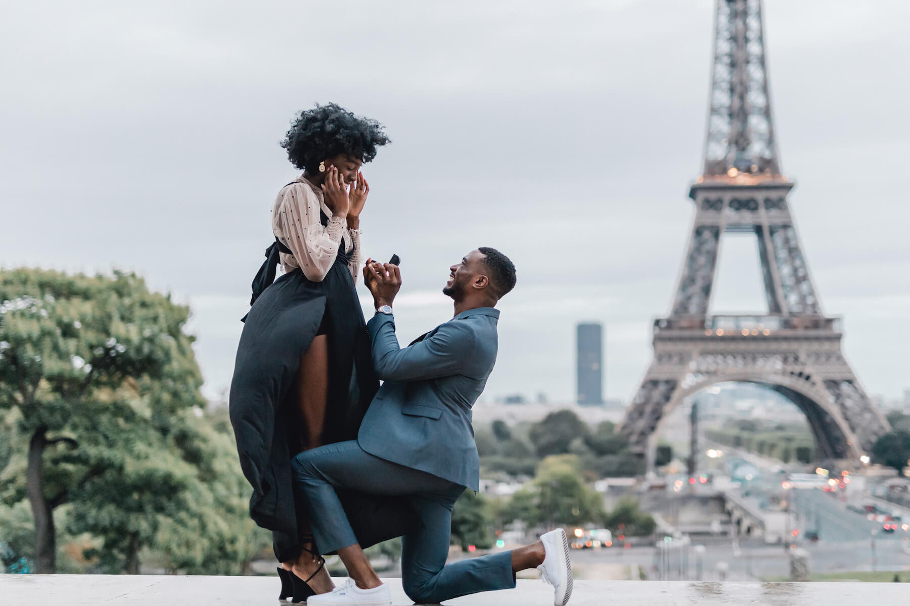 Man is proposing to the woman in front of the Eiffel tower in Paris, the man and woman are both dressed up in semi-formal attire
