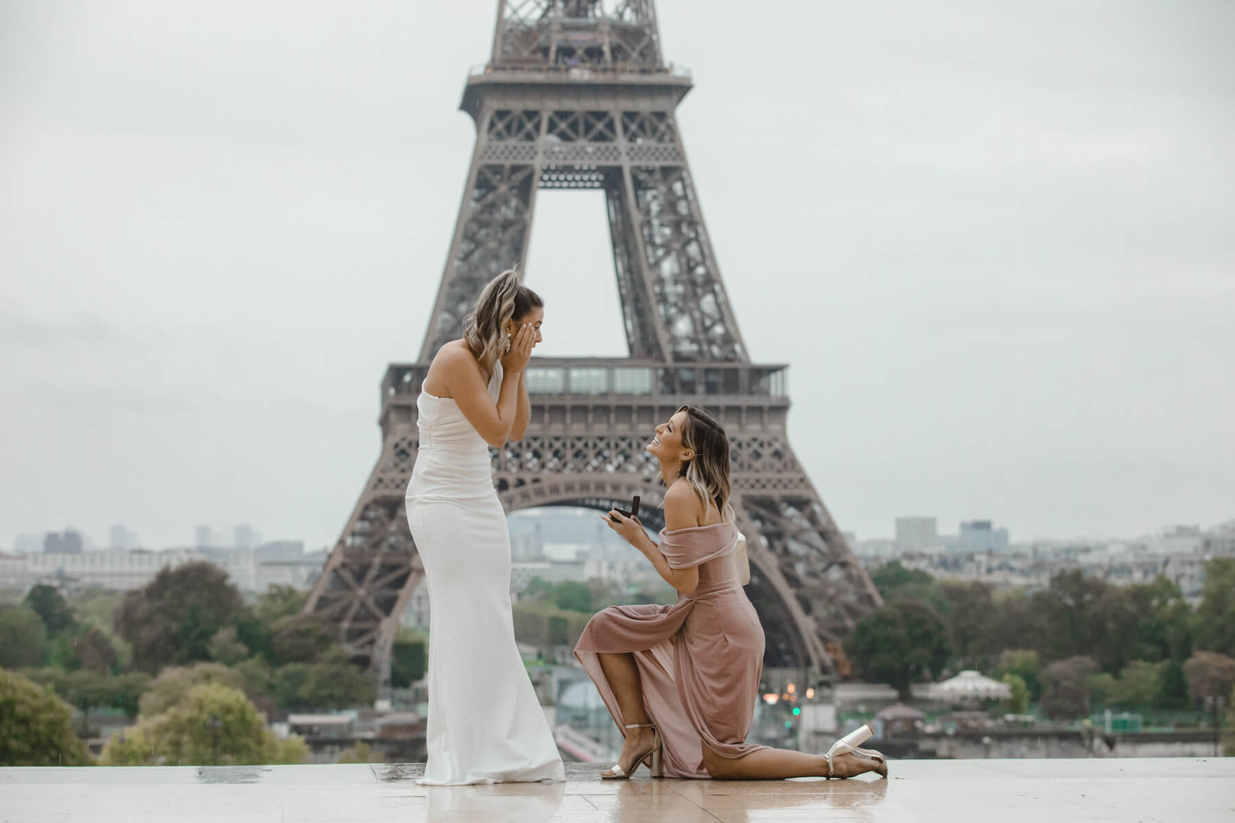 one woman is on one knee proposing to the other woman, both women are wearing formal dresses and are standing in front of the Eiffel Tower in Paris