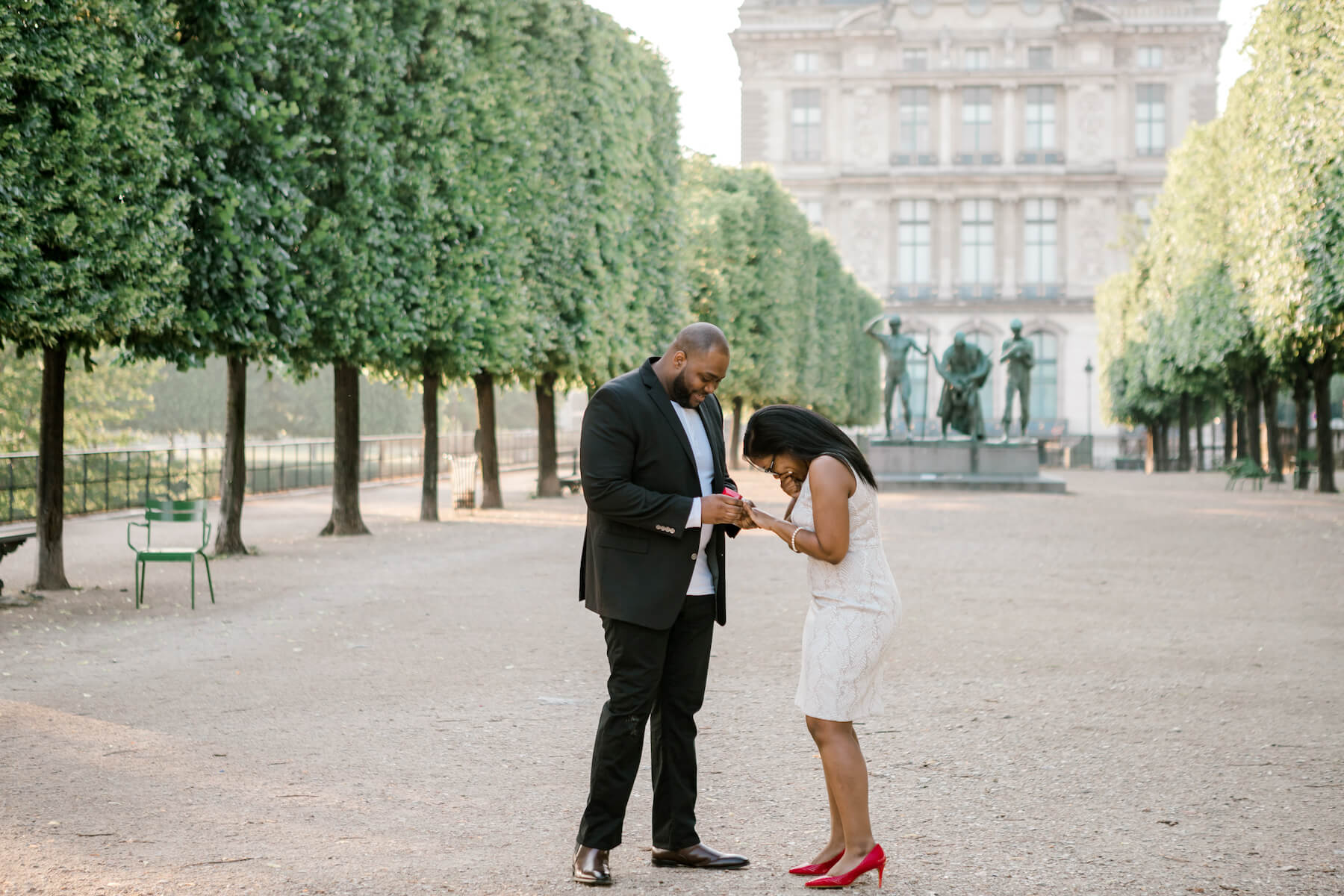 the man is proposing to the woman in Paris, both are wearing formal attire.