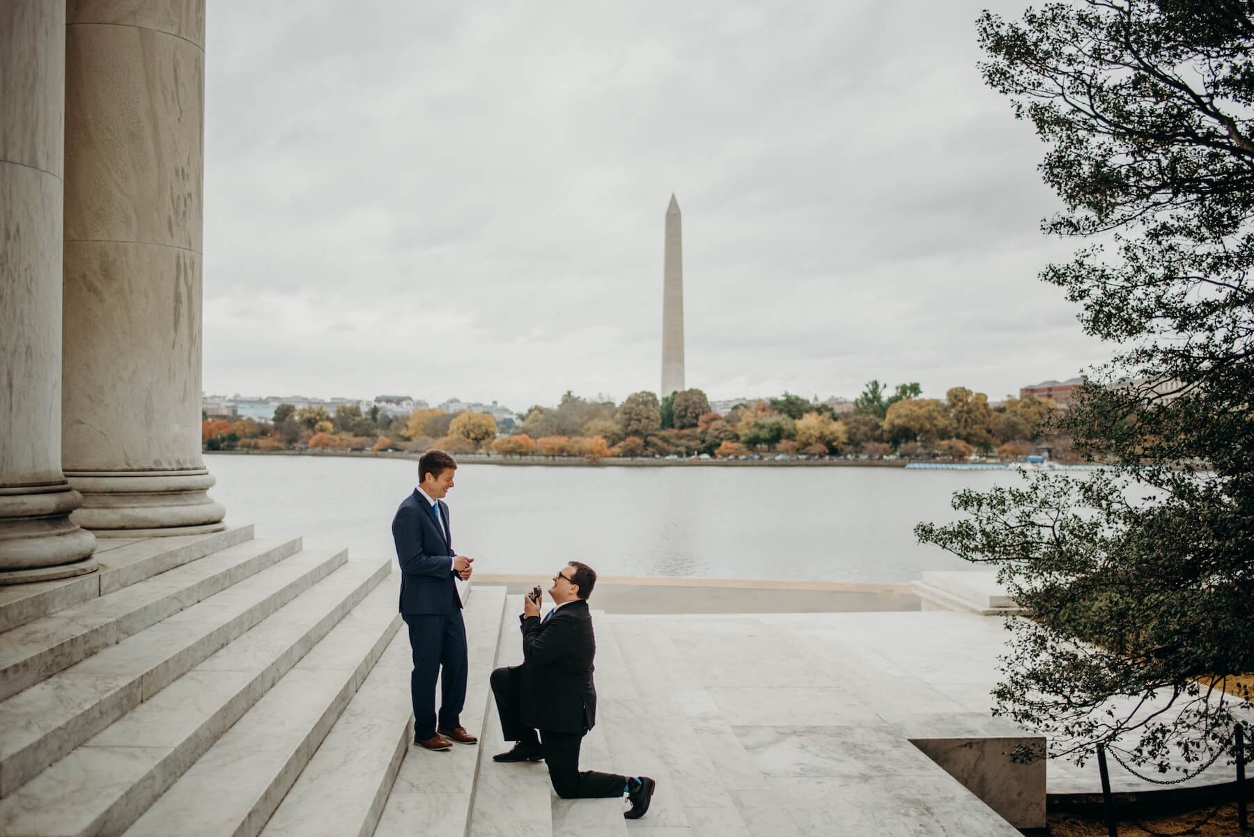 A man is proposing to another man in Washington, DC. One man is kneeling and the other man is standing.