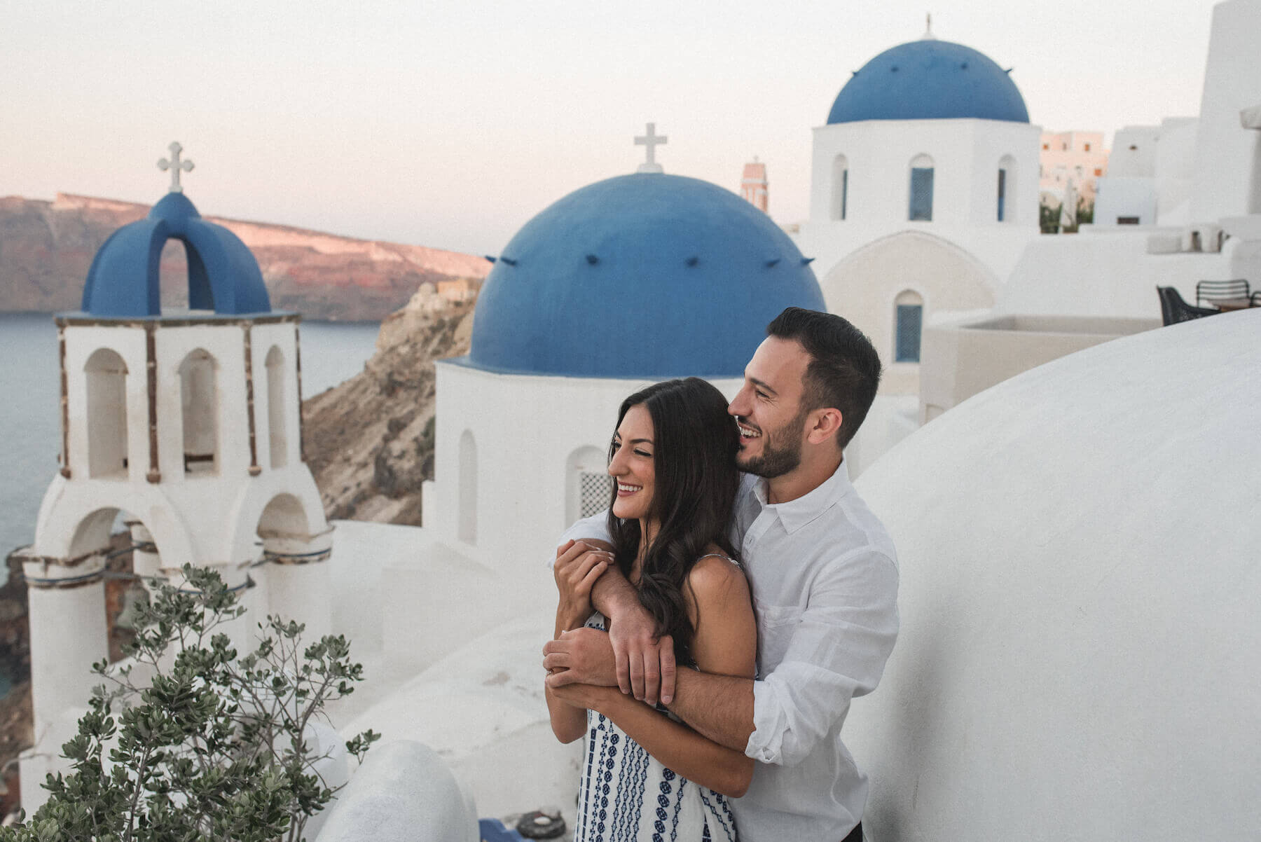 A man is holding a woman after he proposed in Santorini.