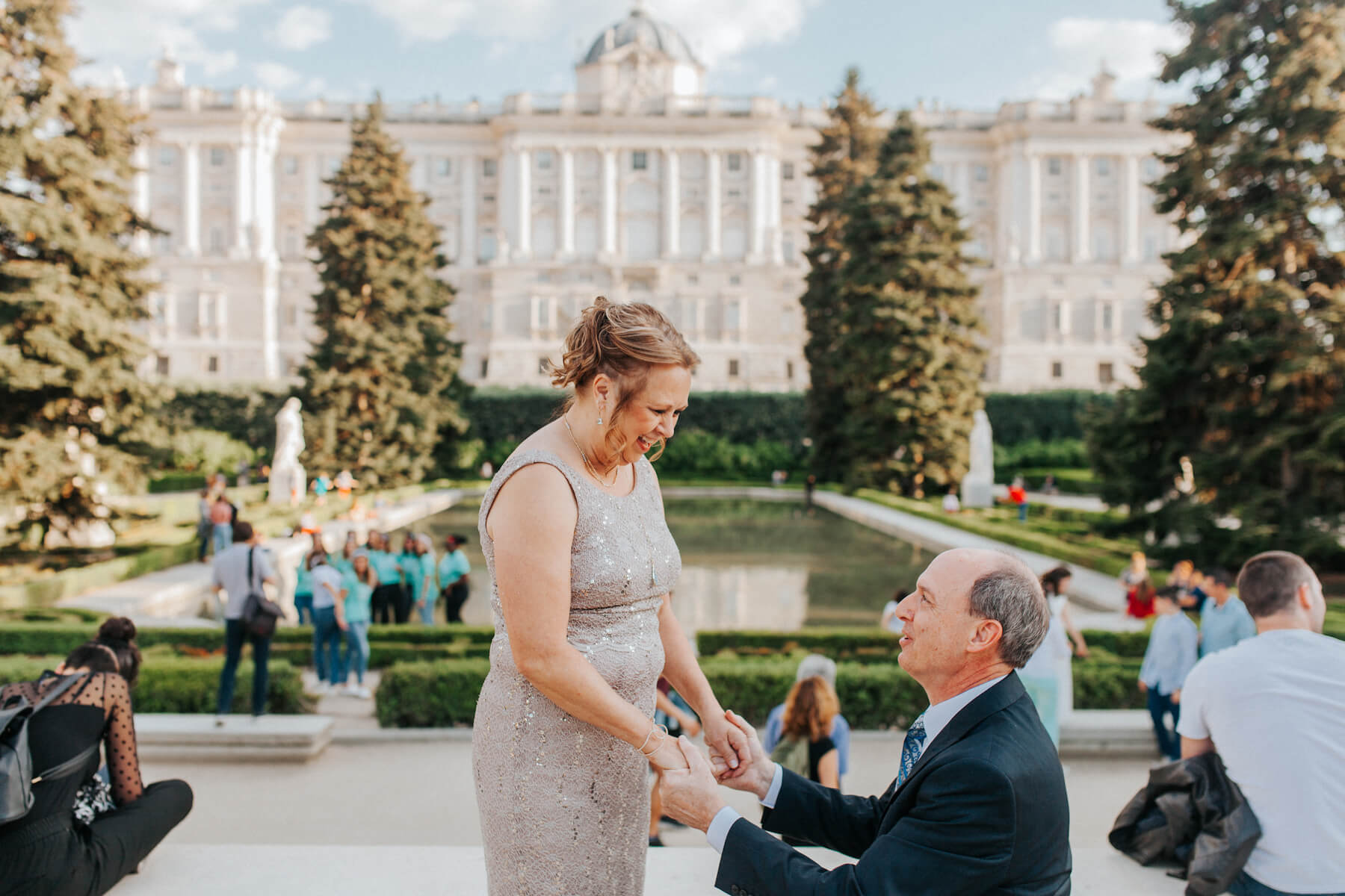 a man is on one knee proposing to a woman wearing formal dress in Madrid