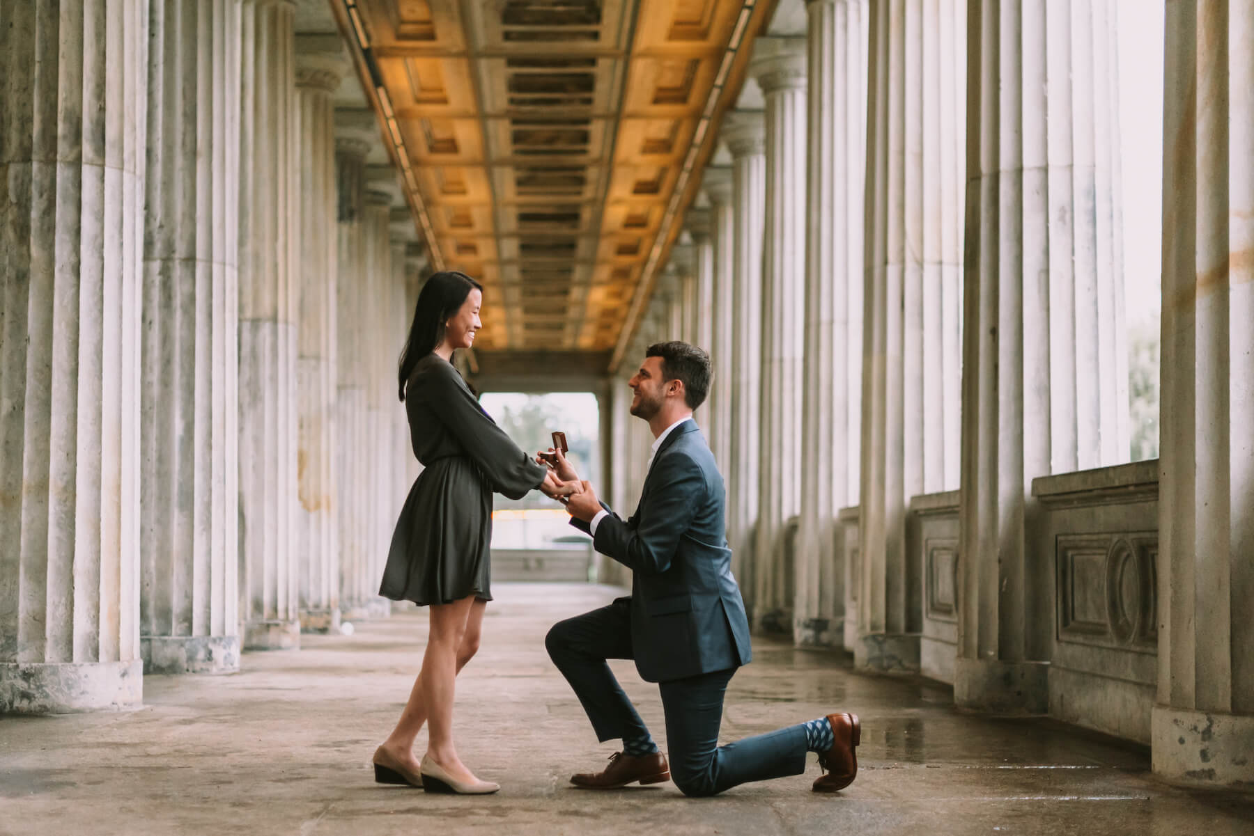 A man is holding a woman's hand and is on one knee proposing. They are standing in a historical walkway in Berlin.