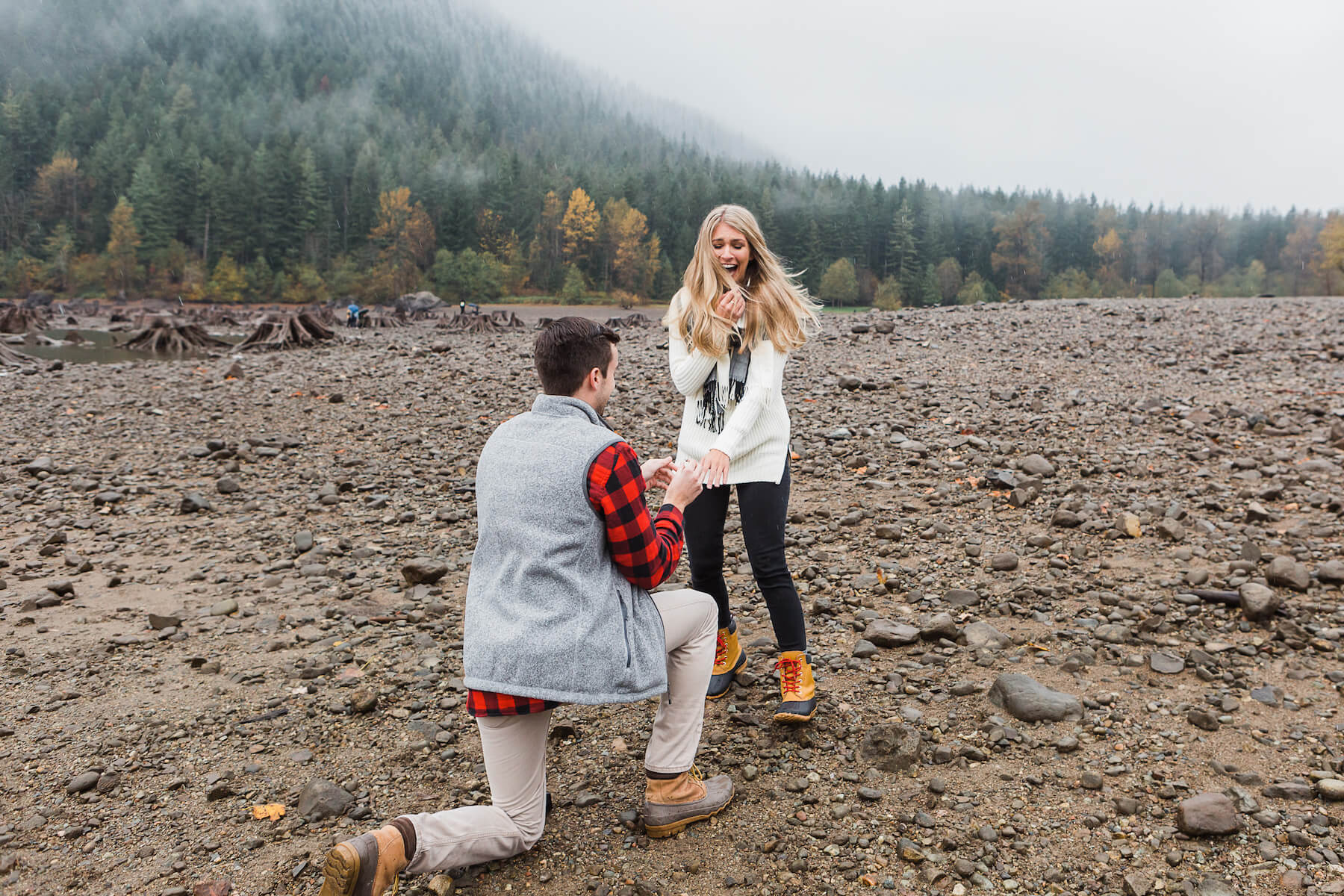 Man is on one knee proposing to a woman on a beach in Seattle. The woman and man are in coordinated outfits and the woman looks surprised.