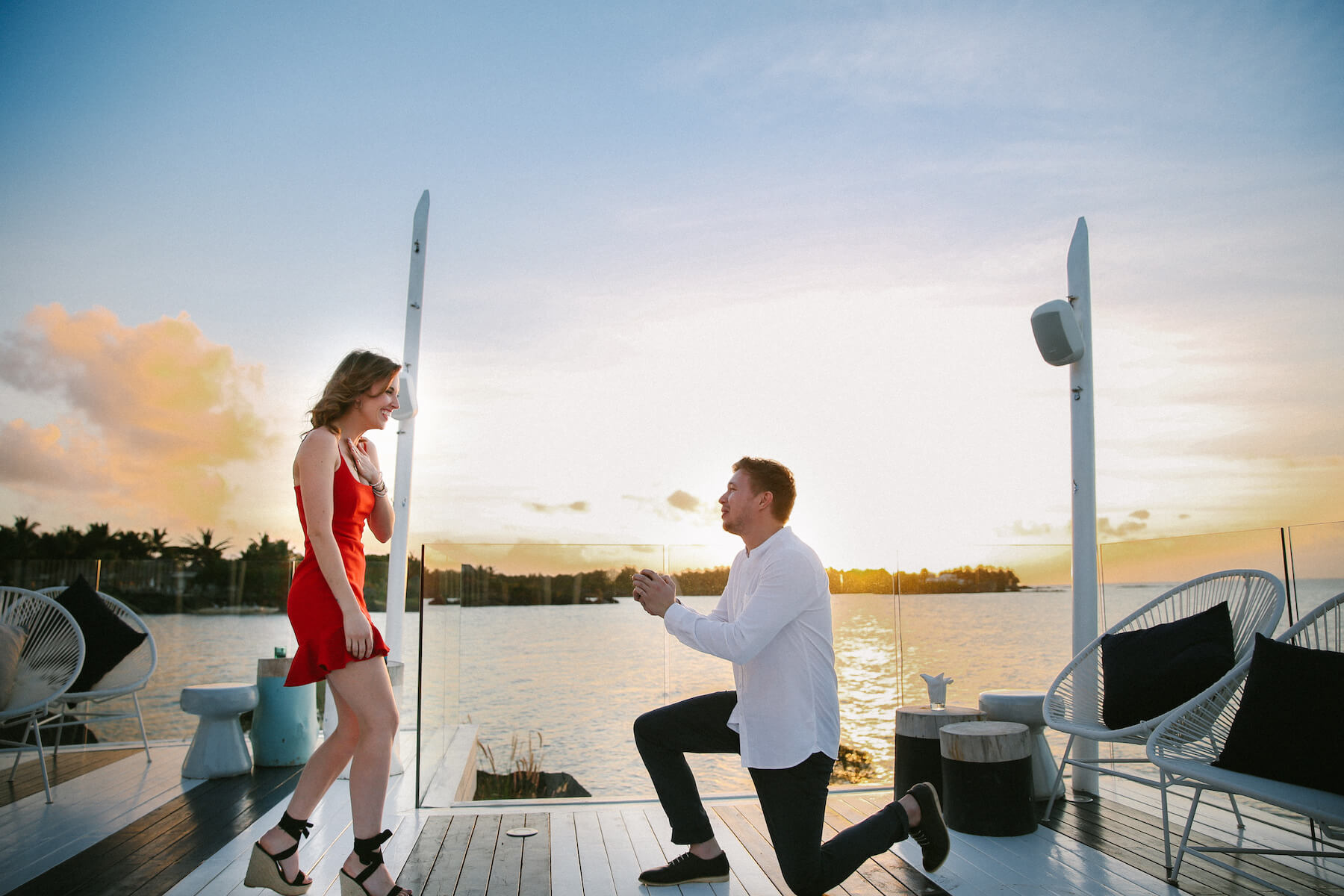 Woman wearing a red dress is being proposed to on a doc in Mauritius