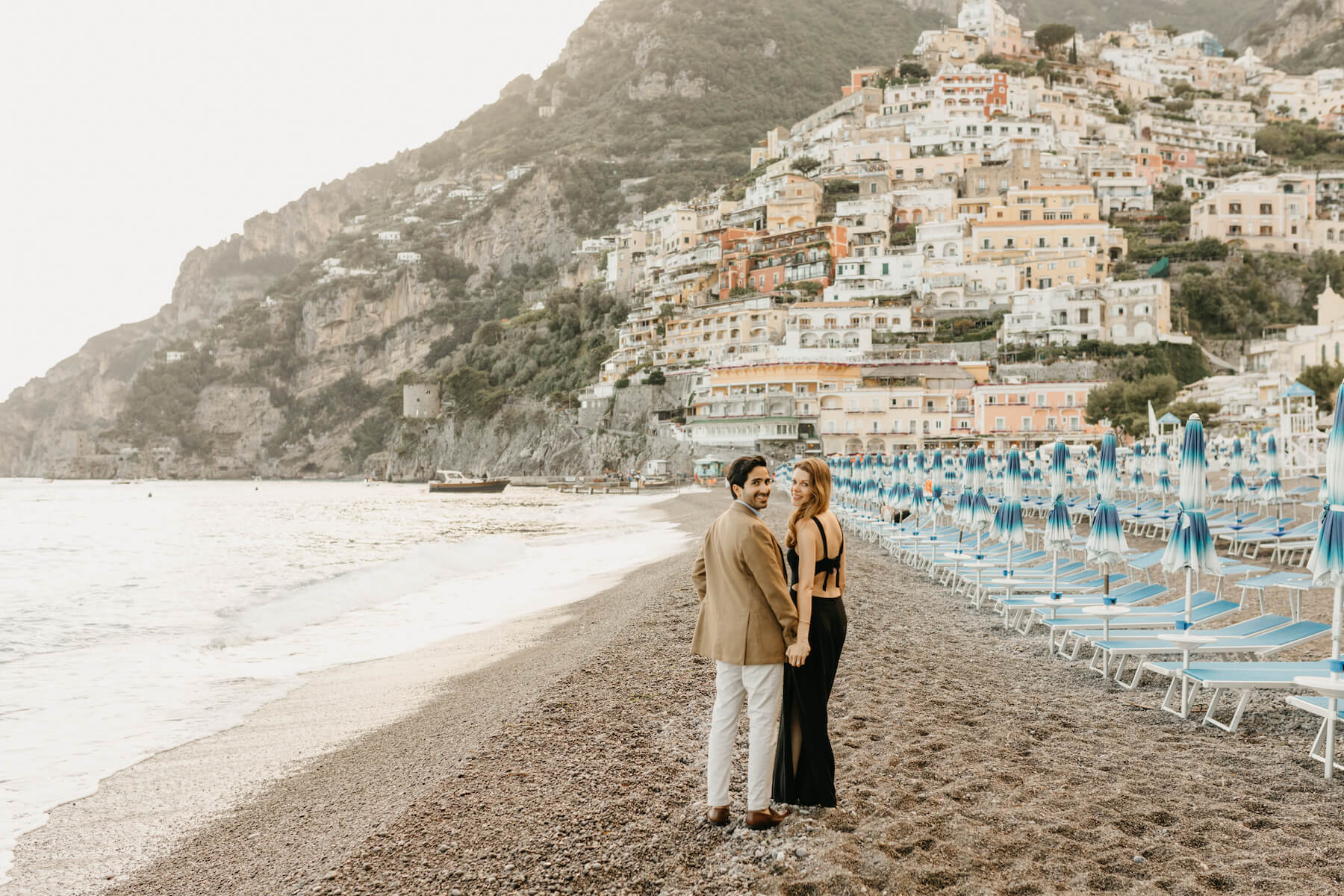 the man and woman are walking on the beach in Positano after the proposal moment