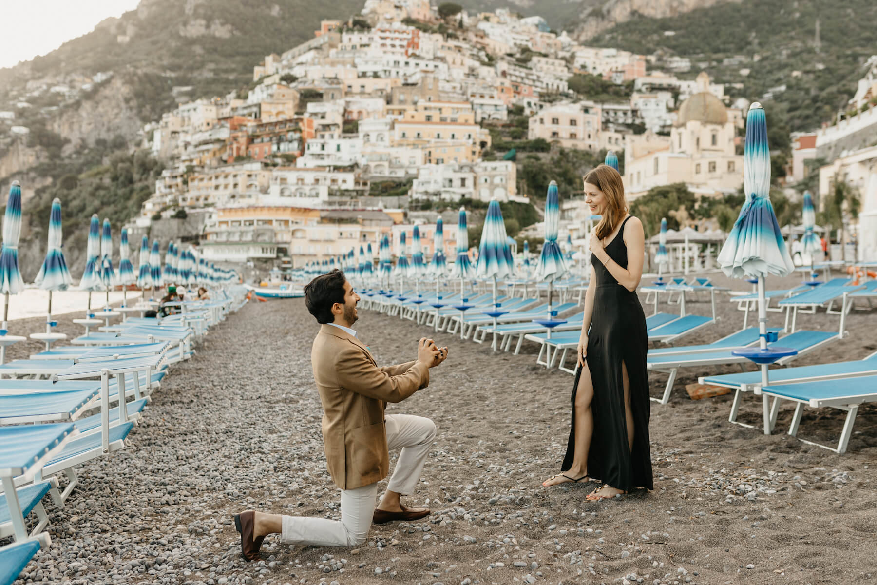 man is proposing to a woman and is on one knee on the beach in Positano, both are wearing semi-formal attire