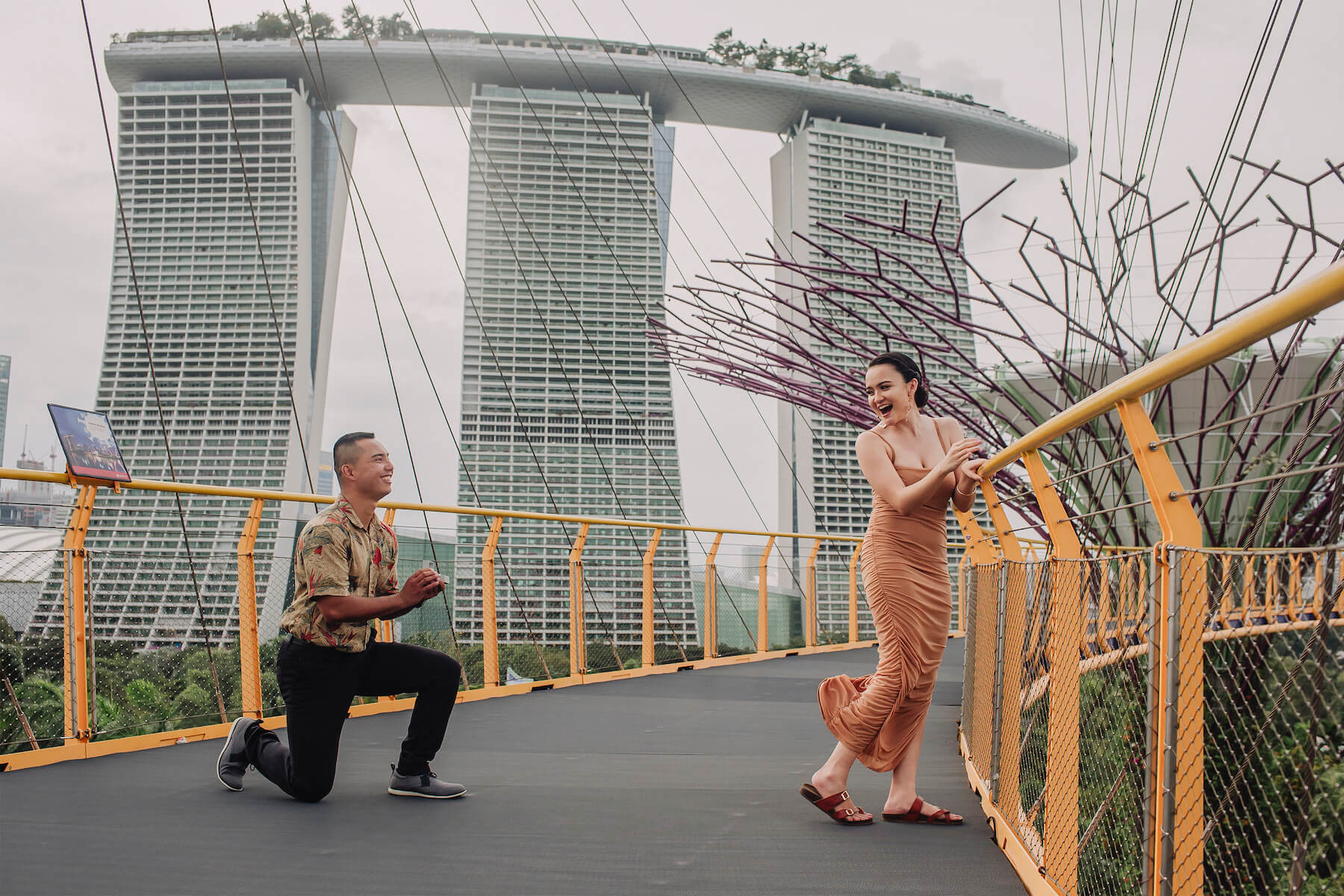 a woman wearing a taupe coloured dress is being proposed to on a bridge in Singapore, the man is wearing a colourful shirt and is on one knee