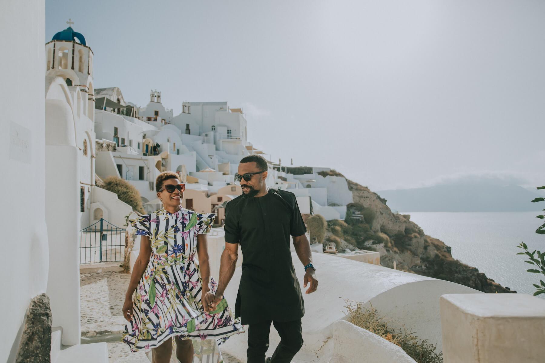 couple walking on a street in Santorini Greece on a Flytographer photo shoot