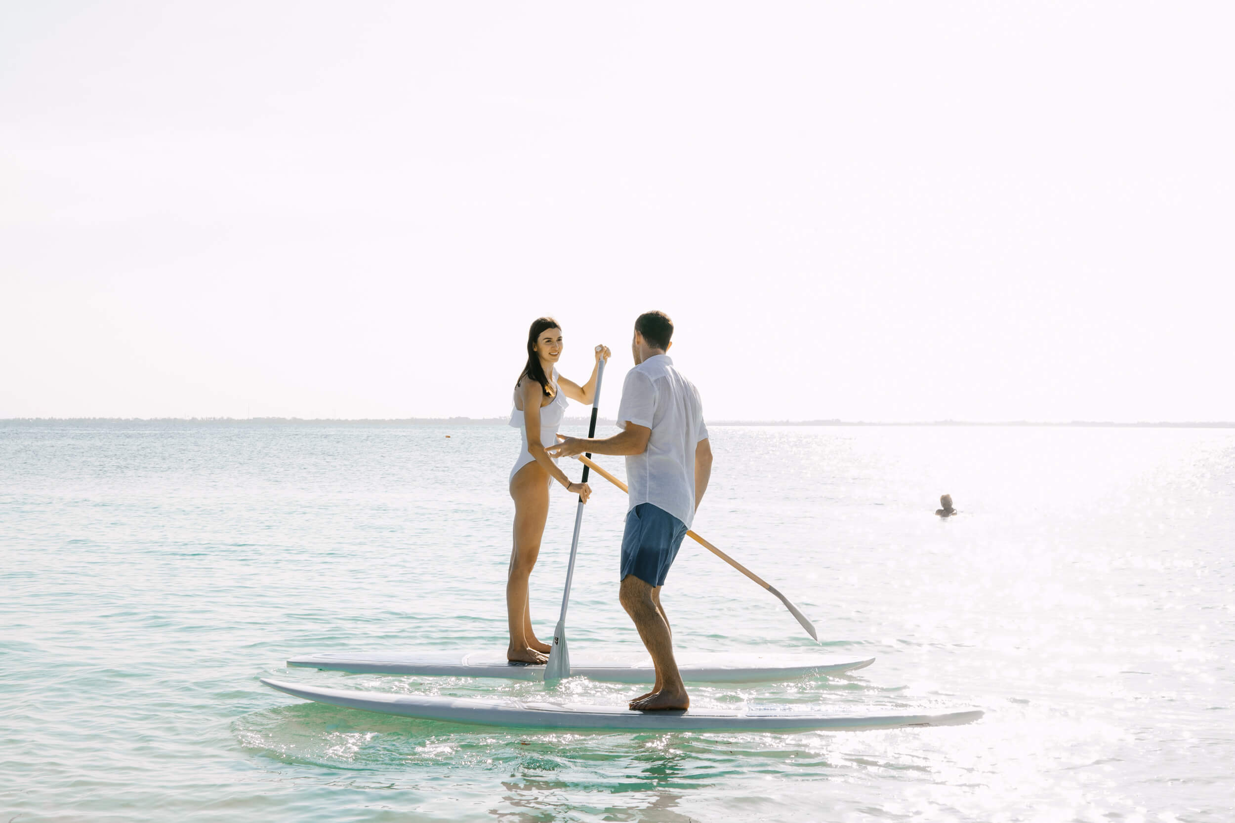 couple on paddle boards in Zanzibar on a Flytographer Photo shoot