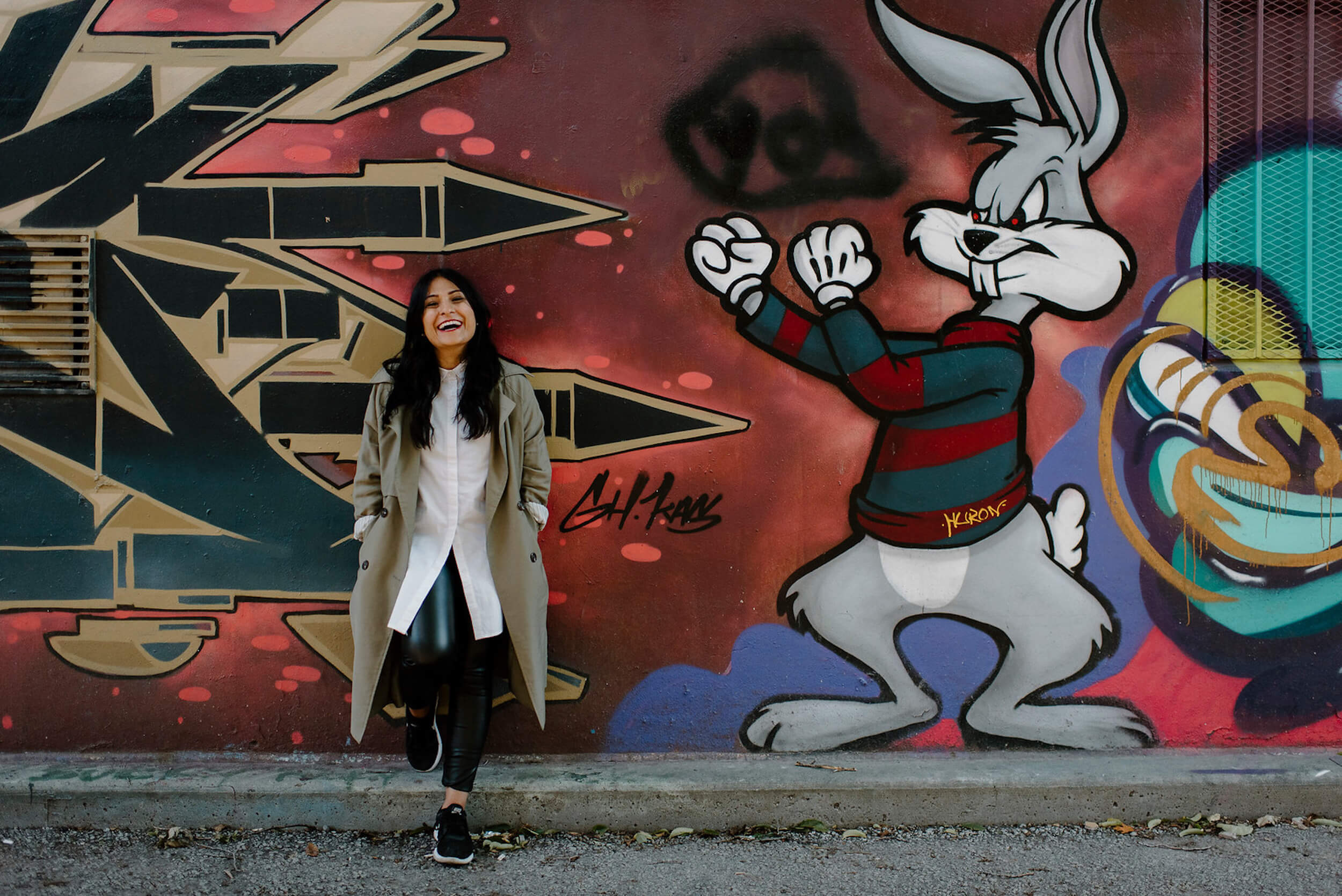 Woman standing in front of a colourful wall laughing in Toronto, Ontario