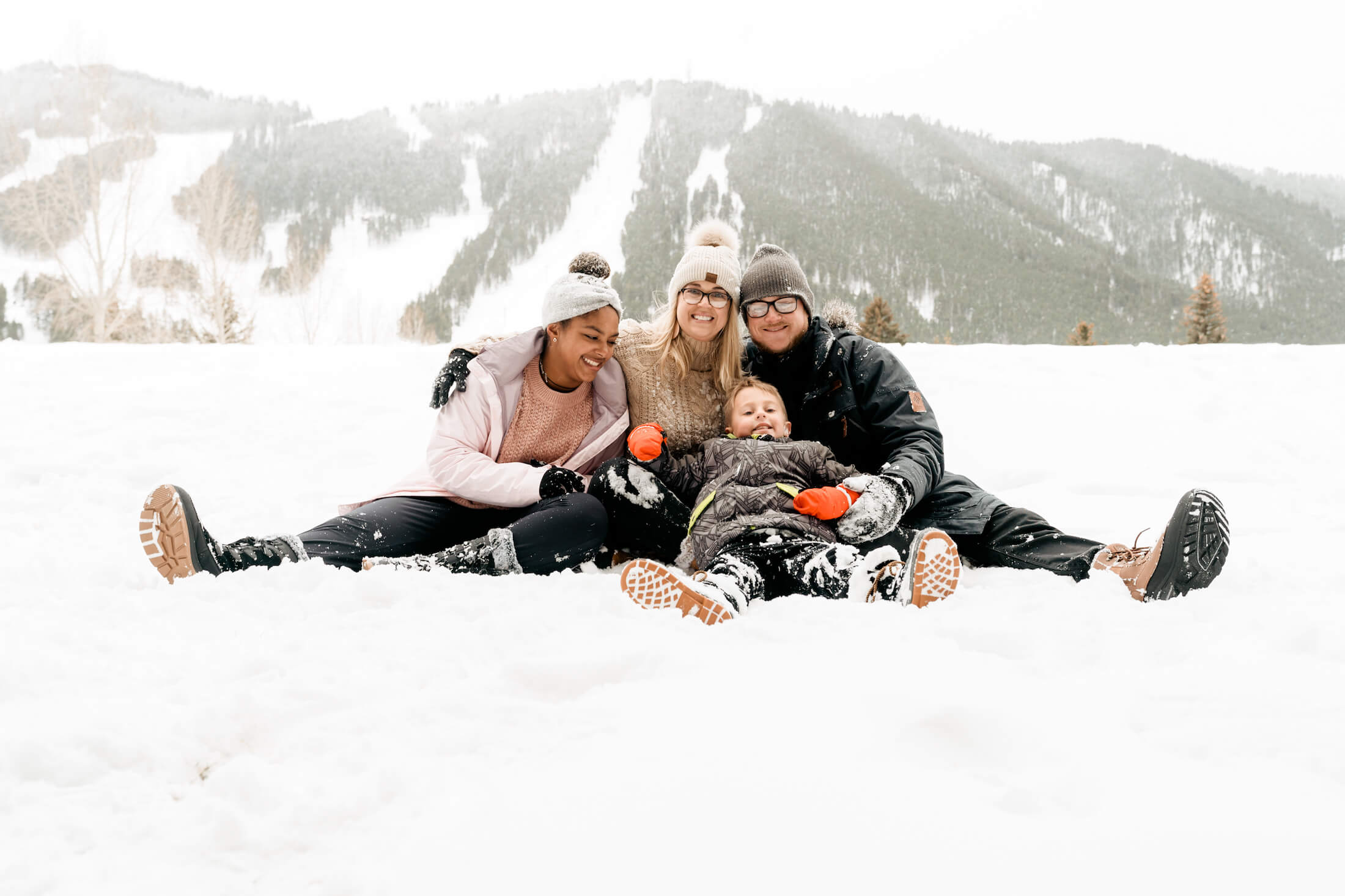 family of 4 sitting in the snow in town square in Jackson Hole, Wyoming