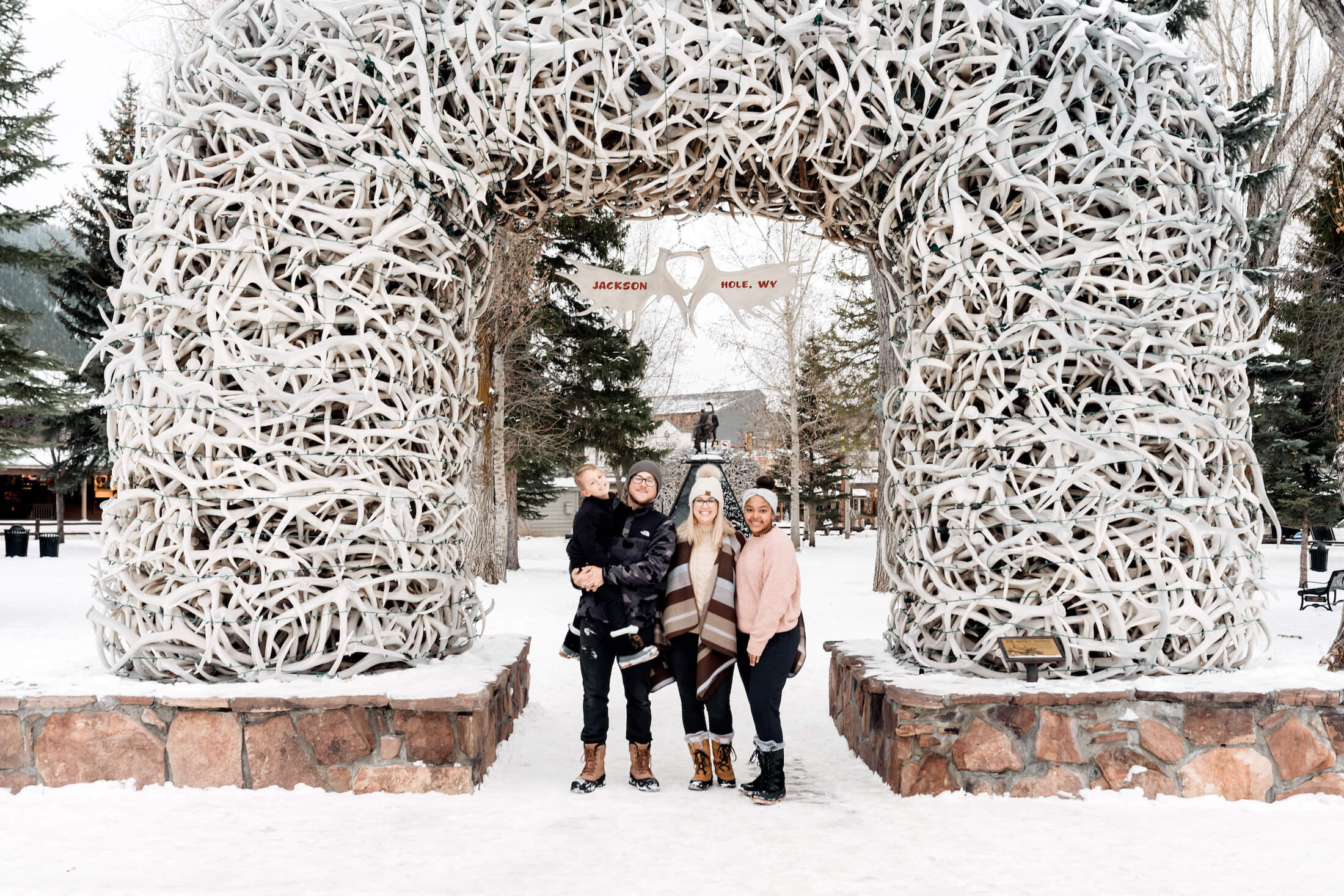 family of 4 standing in front of the antlers in town square in Jackson Hole, Wyoming