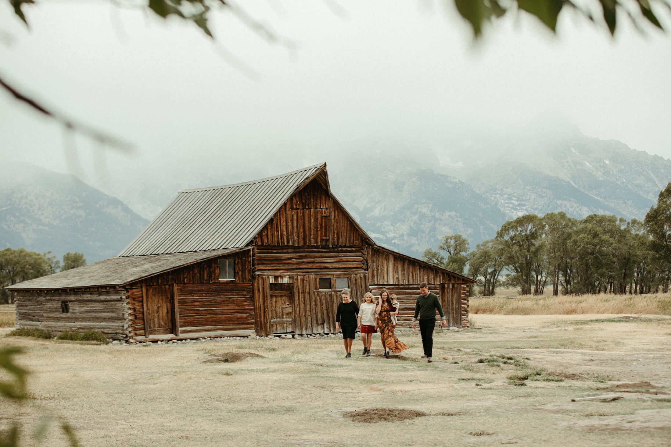 Family of 4 walking in front of a red barn in Jackson Hole, Wyoming
