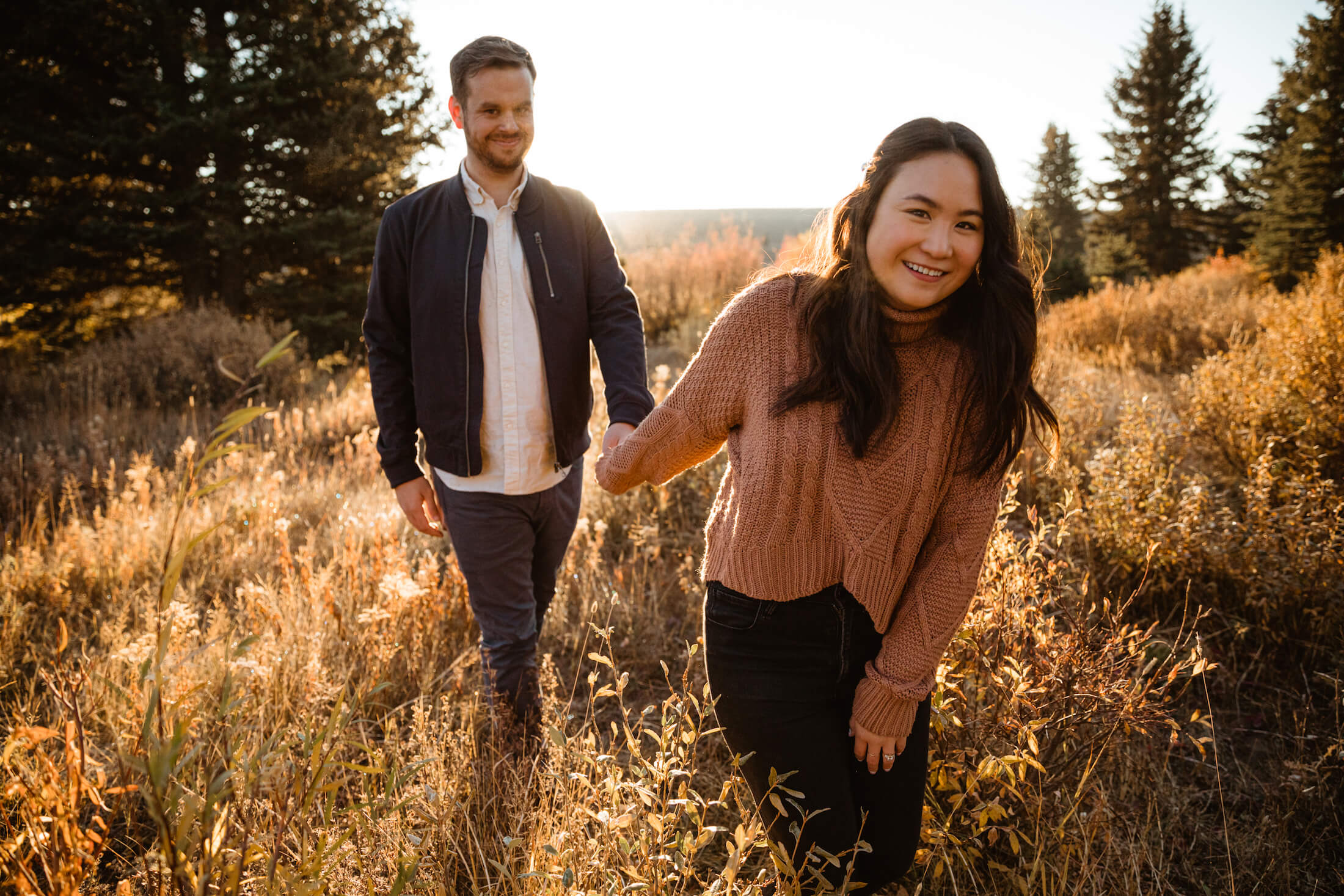 Couple holding hands and walking in a field in Jackson Hole, Wyoming