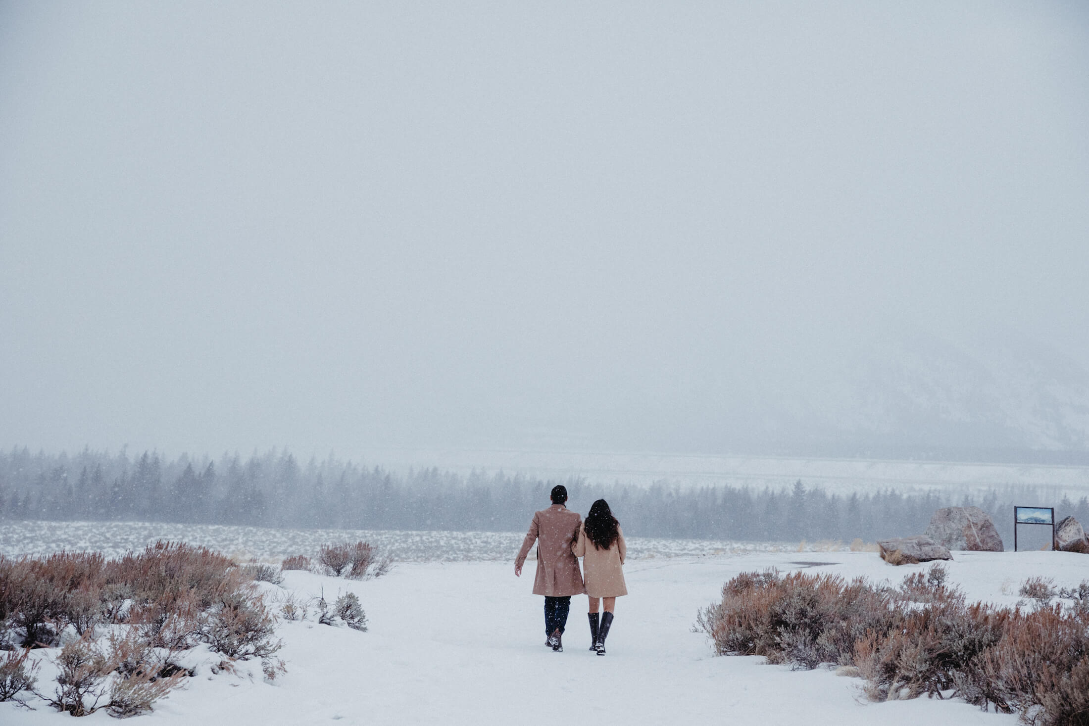 Couple walking in the snow in Jackson Hole, Wyoming