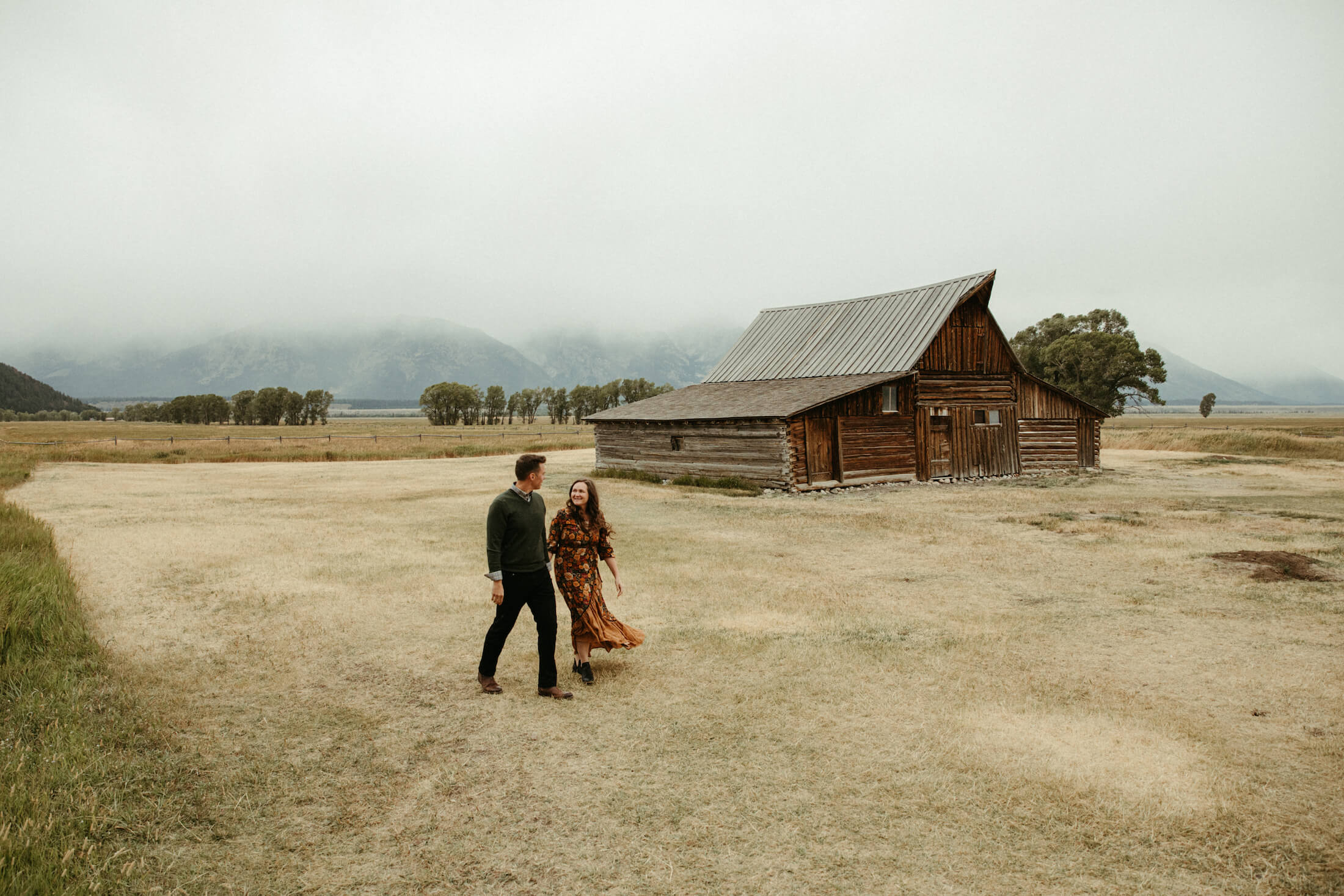 Couple walking in front of a red barn in Jackson Hole, Wyoming