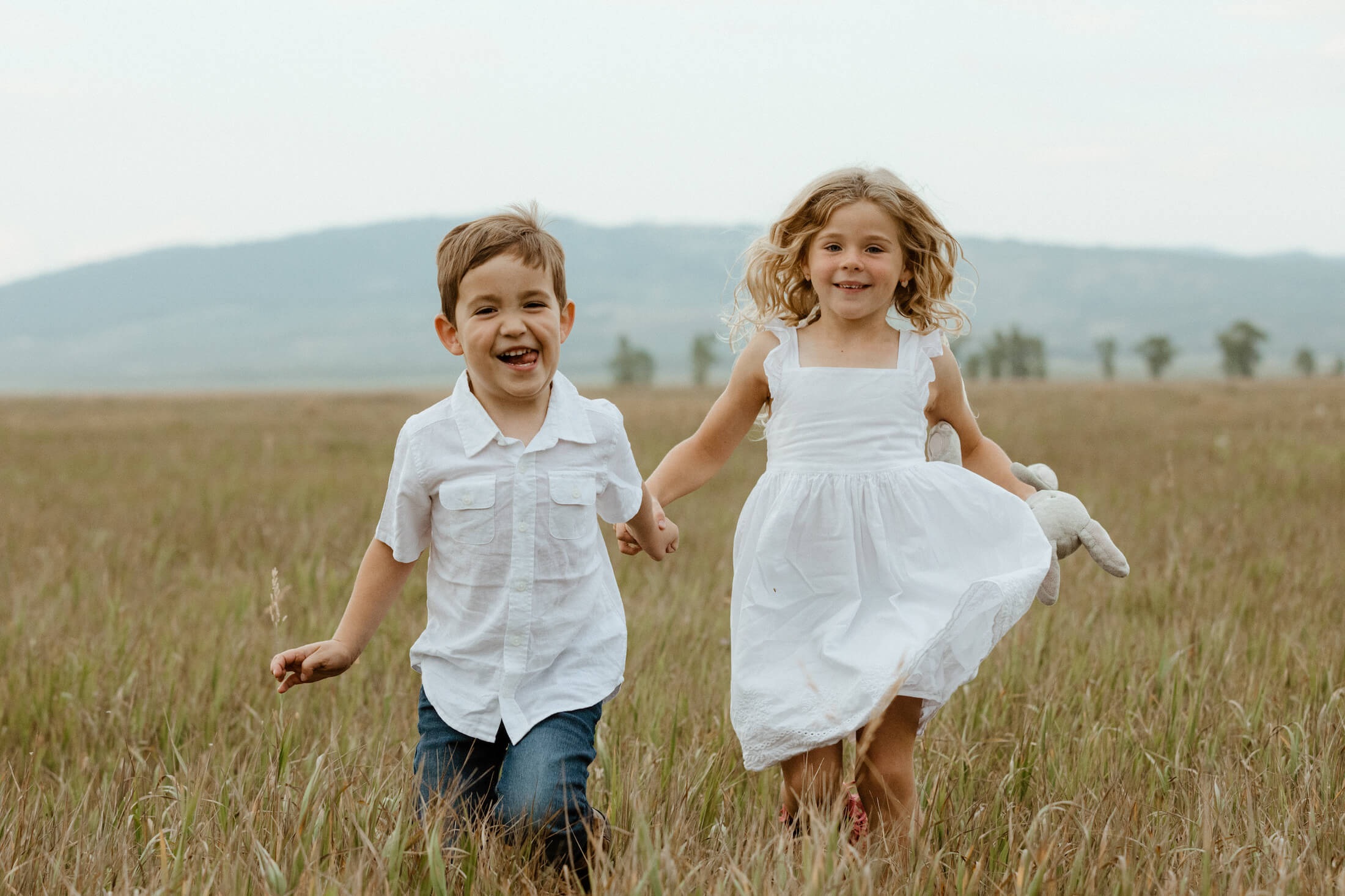 Kids running and holding hands in a field in Jackson Hole, Wyoming