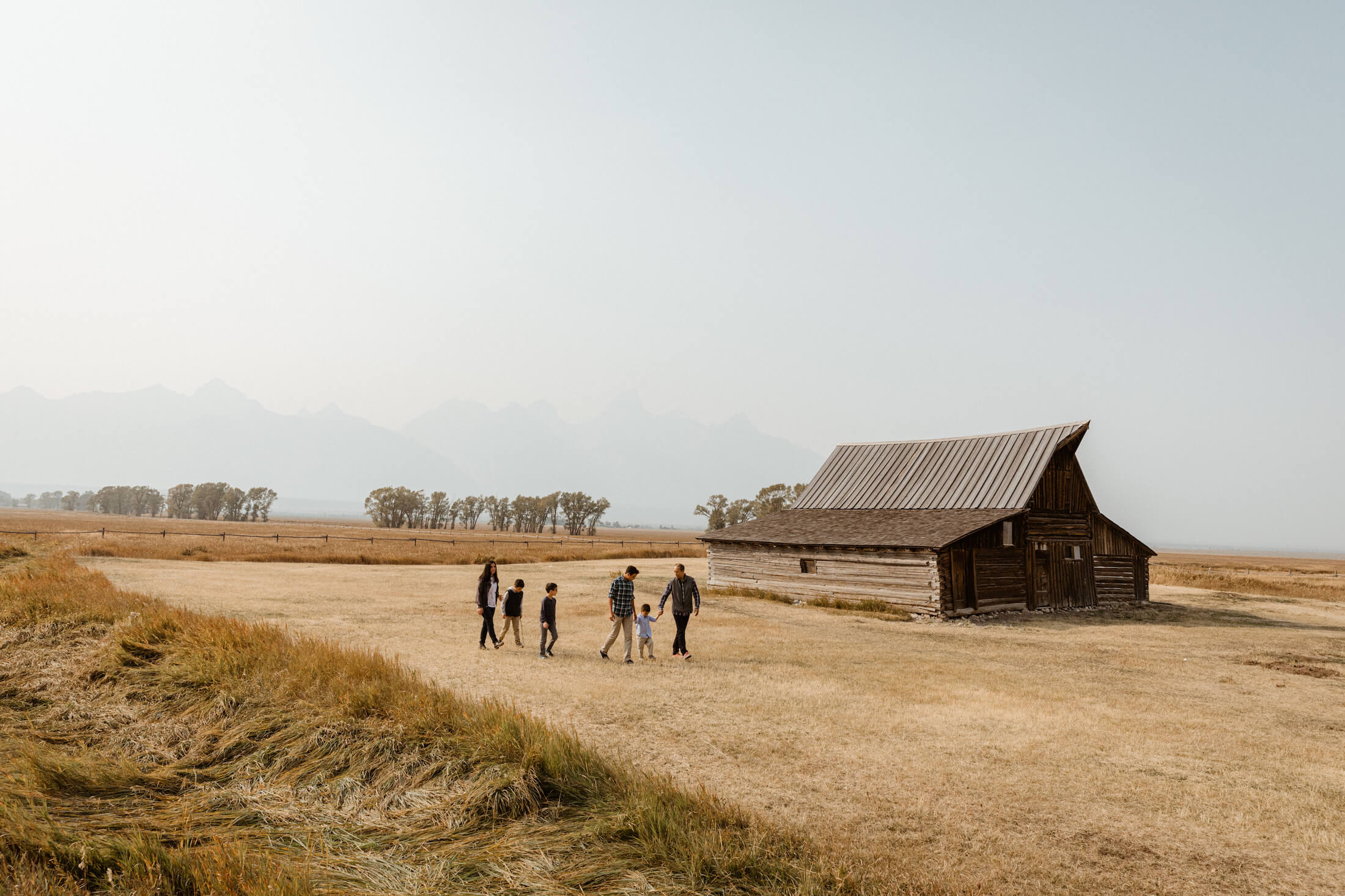 A family walks beside a barn in Jackson Hole, USA