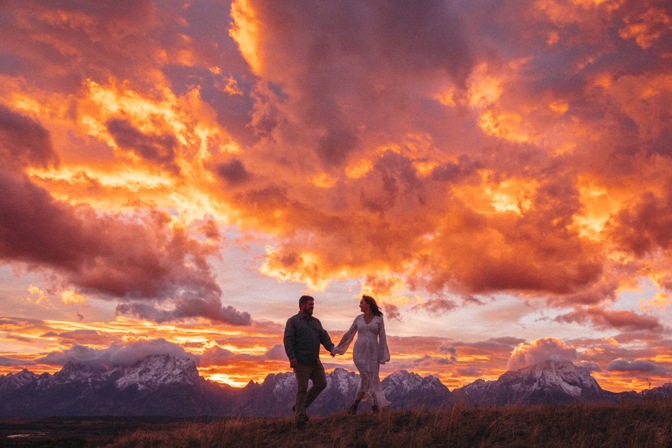 Couple walking and holding hands with a most beautiful sunset in the background in Jackson Hole, Wyoming