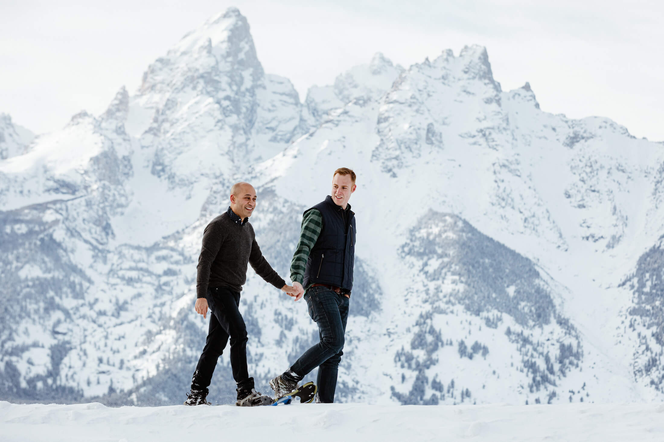 two men are holding hands and walking in the snow in Jackson Hole, Wyoming