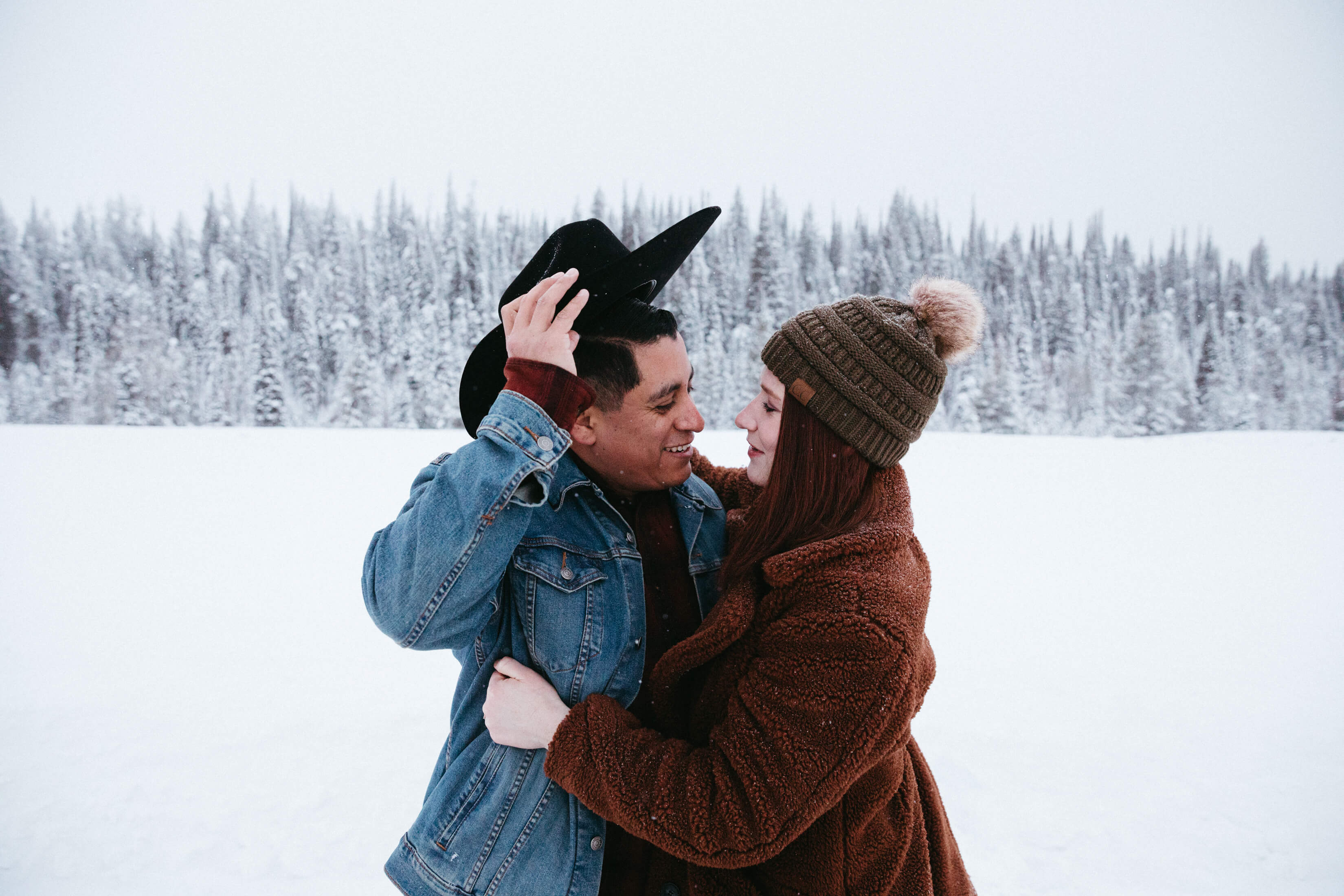 Couple holding each other in the snow in Jackson Hole, Wyoming